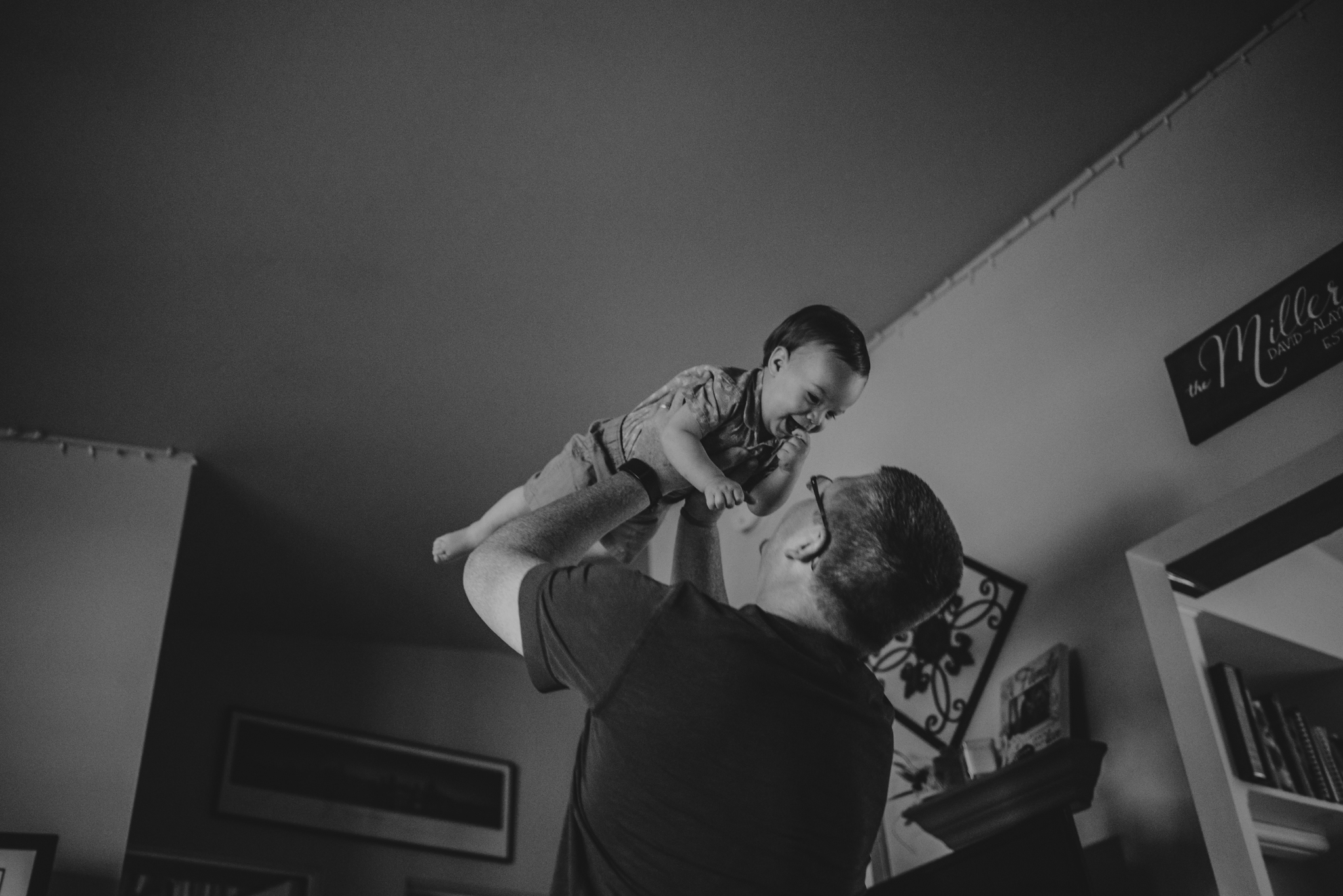 Daddy lifts up baby in an airplane during their lifestyle session at home in Wake Forest with Rose Trail Images.