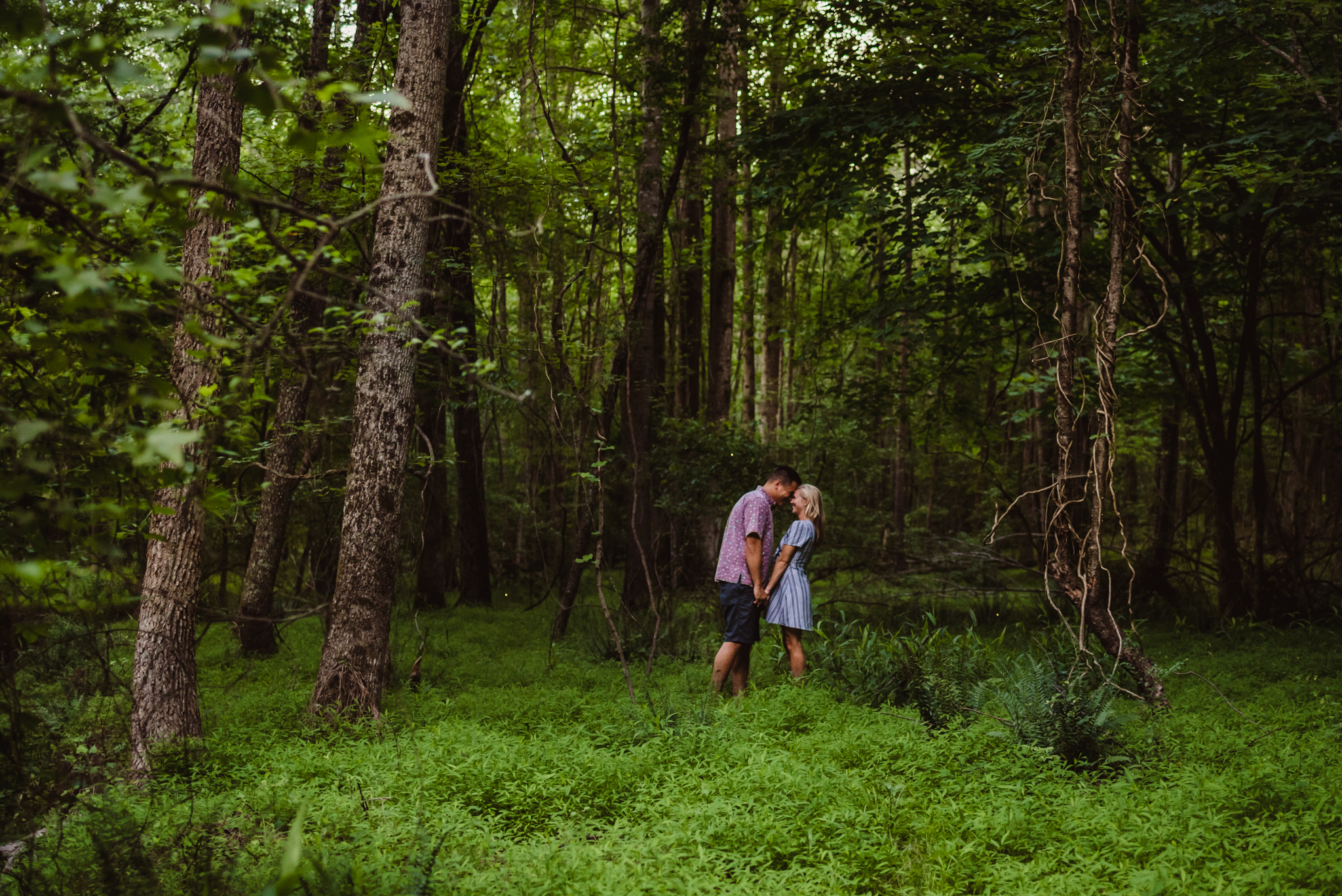 Kristin and Drew walked in the woods and greenery with the lightning bugs for their engagement pictures in Raleigh with Rose Trail Images.