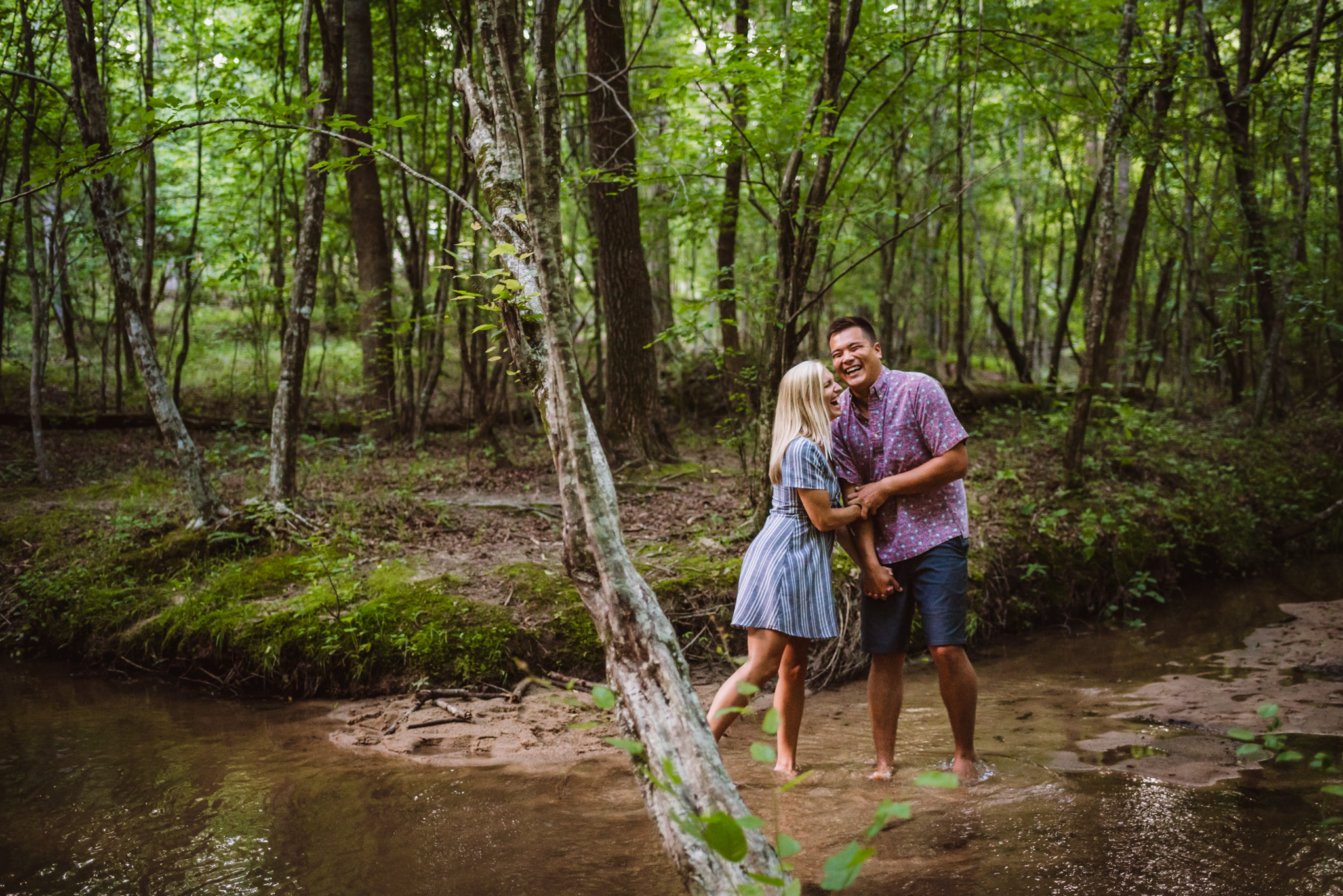 Kristin and Drew laughed together on the banks of the creek for their engagement pictures in Raleigh with Rose Trail Images.