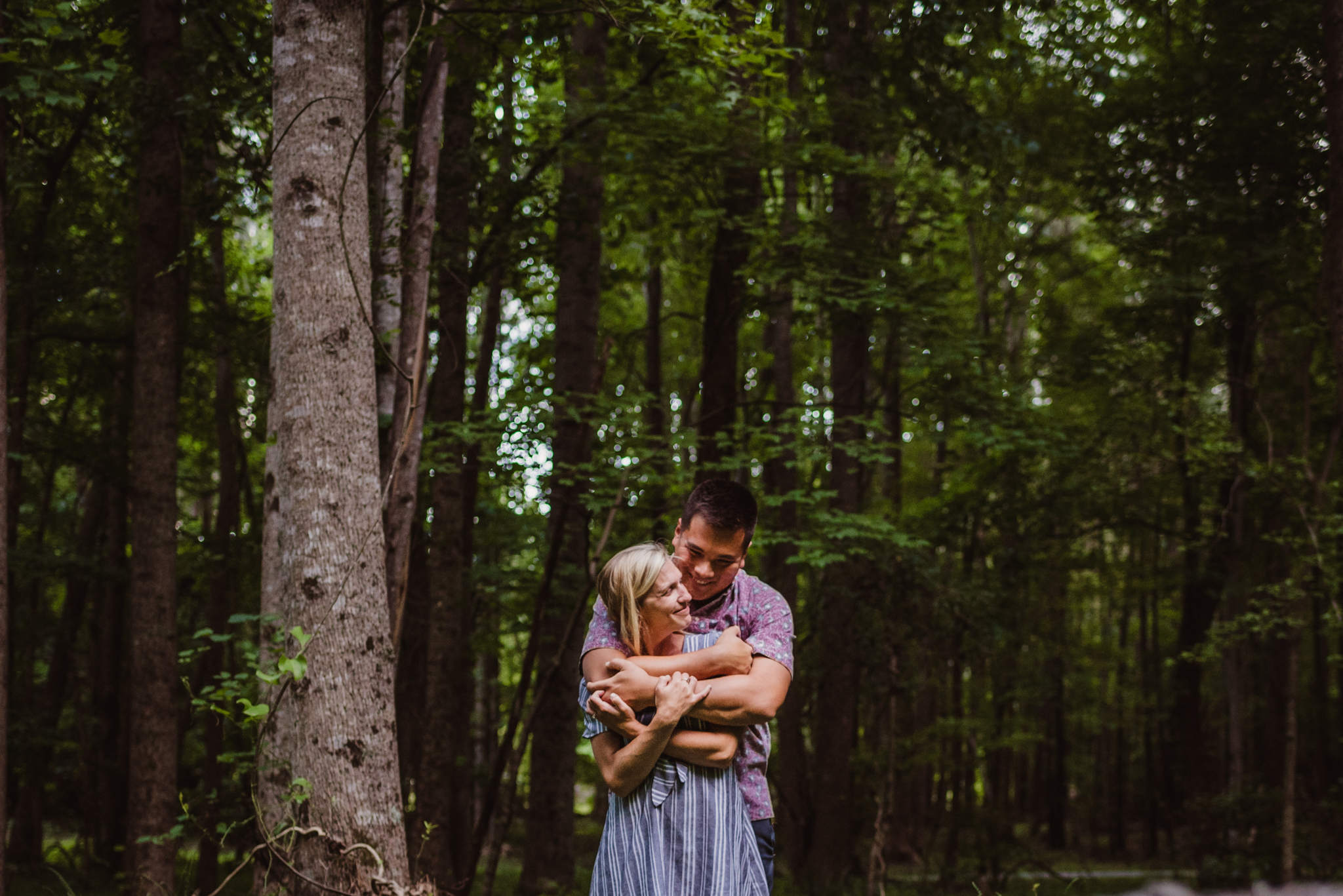 Kristin and Drew hugged each other in the woods during their engagement shoot in Raleigh with Rose Trail Images.
