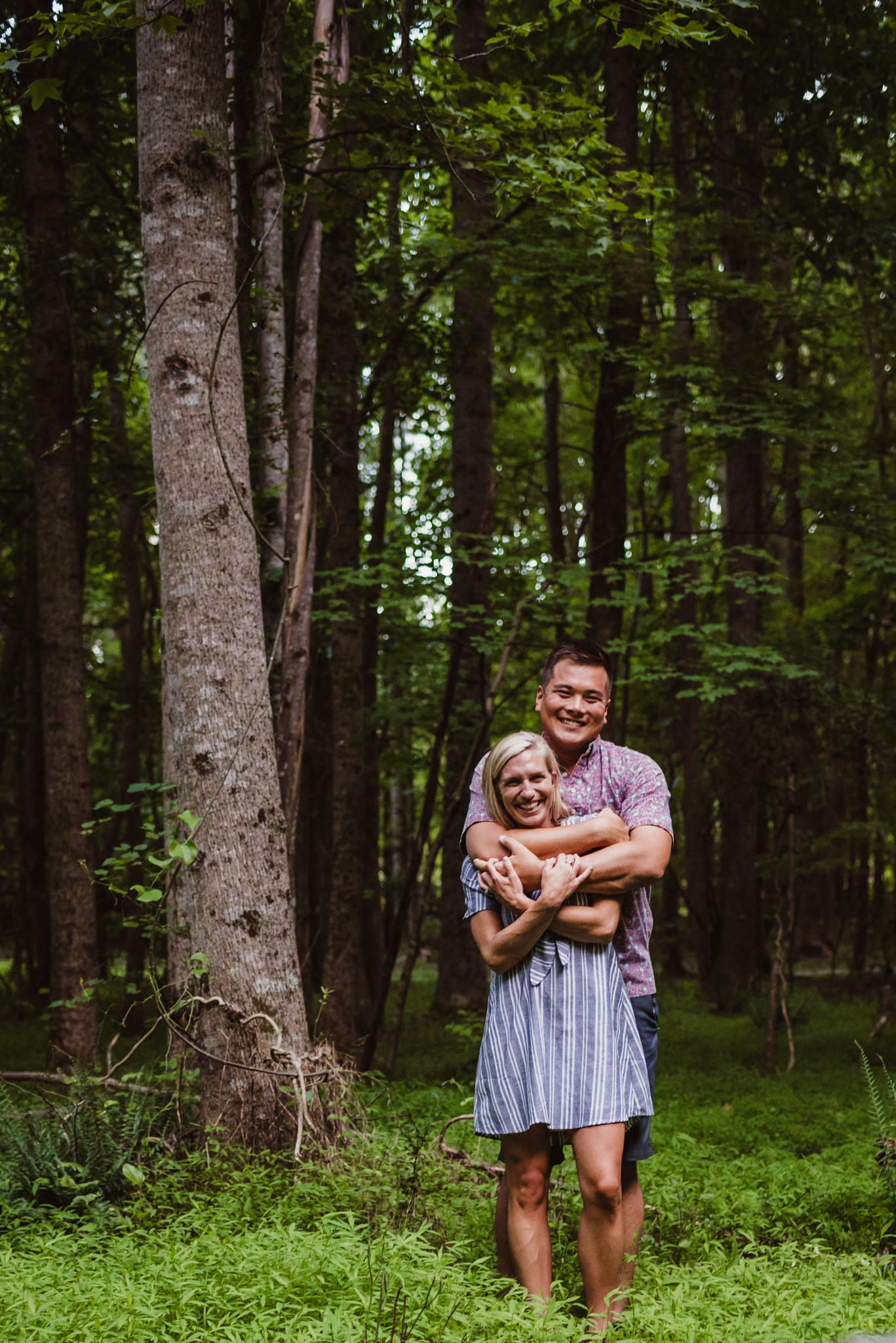 Kristin and Drew hugged and laughed in the woods during their engagement shoot in Raleigh with Rose Trail Images.
