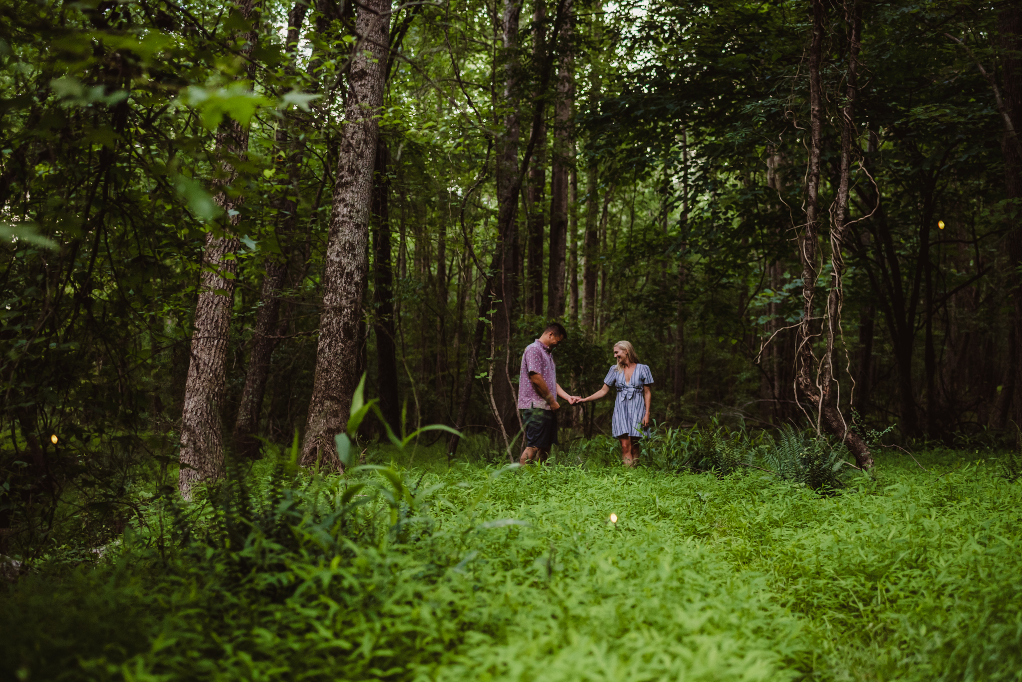 Kristin and Drew held hands in the woods during their engagement shoot in Raleigh with Rose Trail Images.