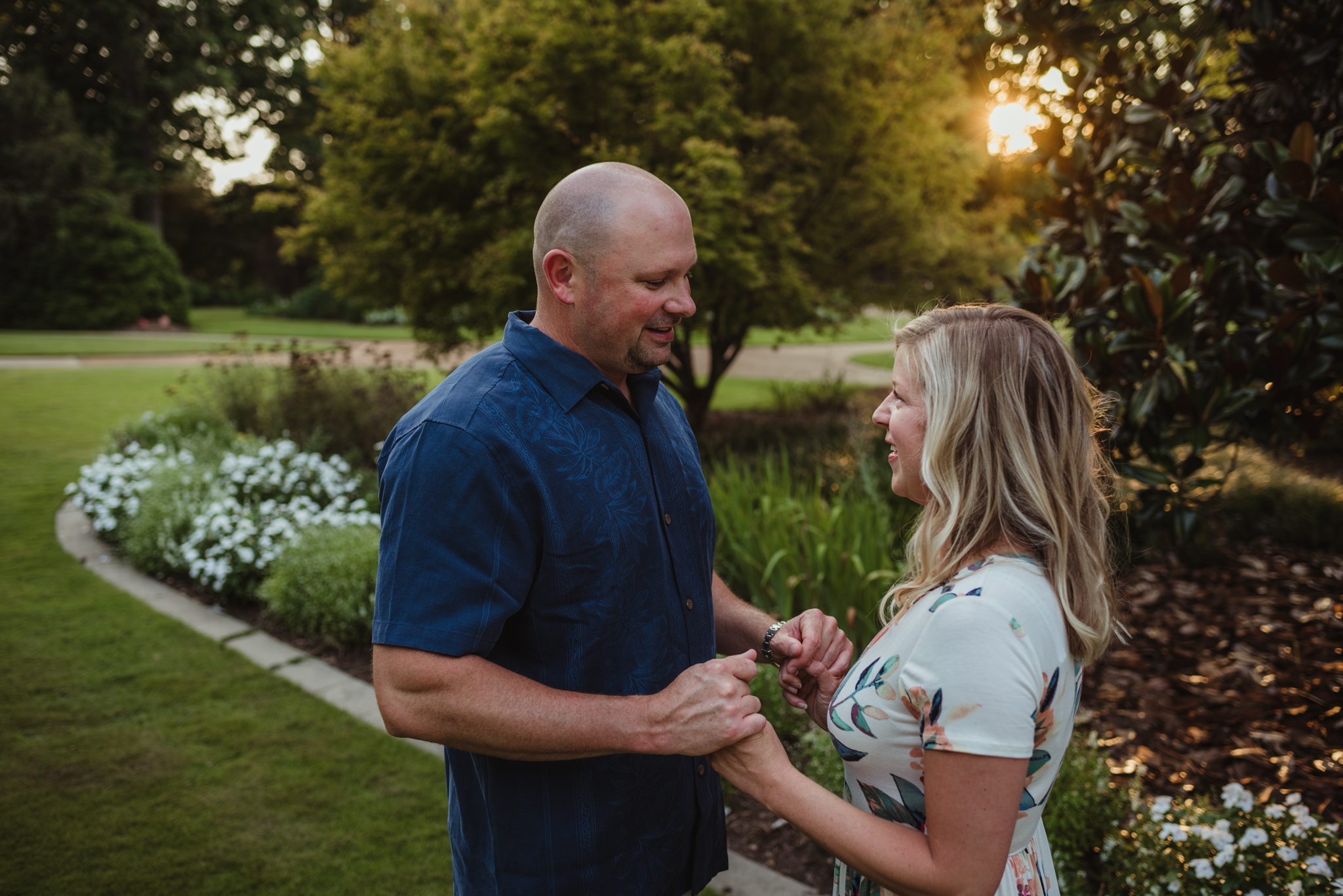 The groom tells me the story of their proposal during their engagement session at Fred Fletcher Park in Raleigh, North Carolina with Rose Trail Images.