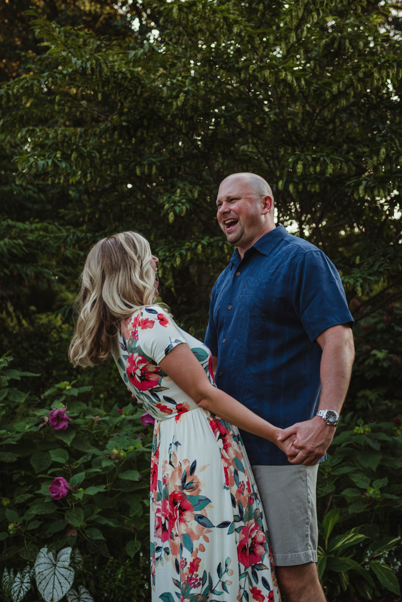 The bride and groom hold hands and laugh during their engagement session at Fred Fletcher Park in Raleigh, North Carolina with Rose Trail Images.