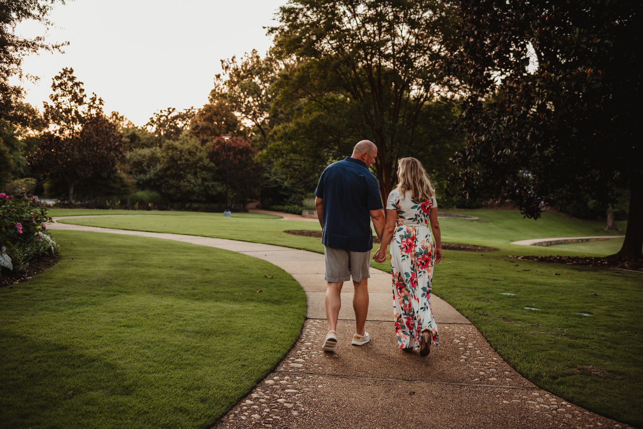 The bride and groom hold hands as they walk down the path during their engagement session at Fred Fletcher Park in Raleigh, North Carolina with Rose Trail Images.