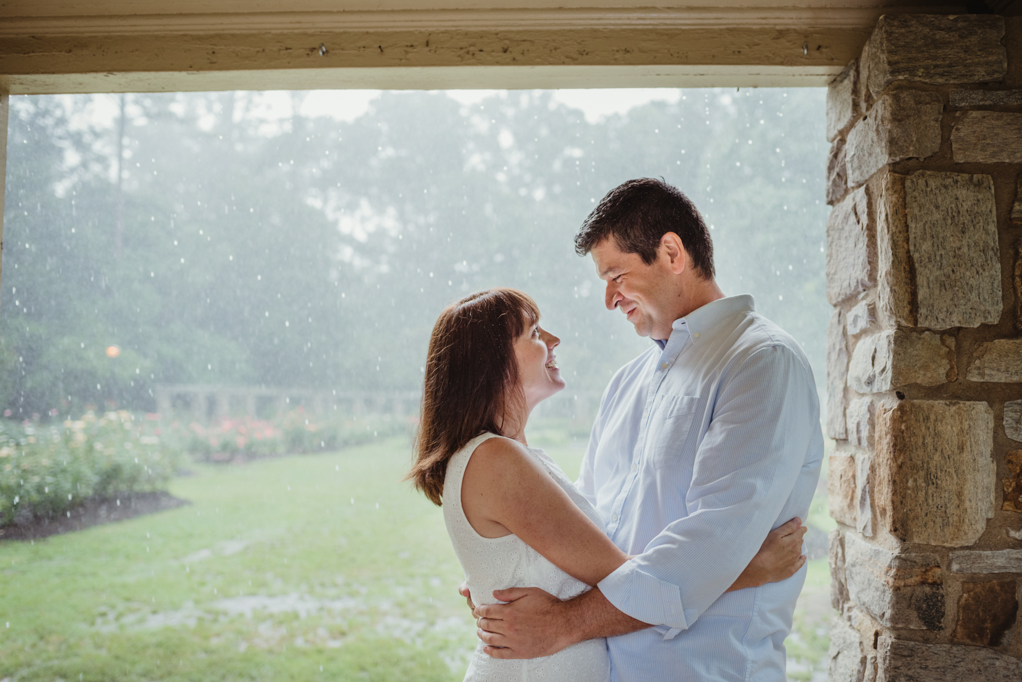 The bride and groom to be hold each other, during their engagement session, in the shelter during the rainstorm in Raleigh, picture by Rose Trail Images.