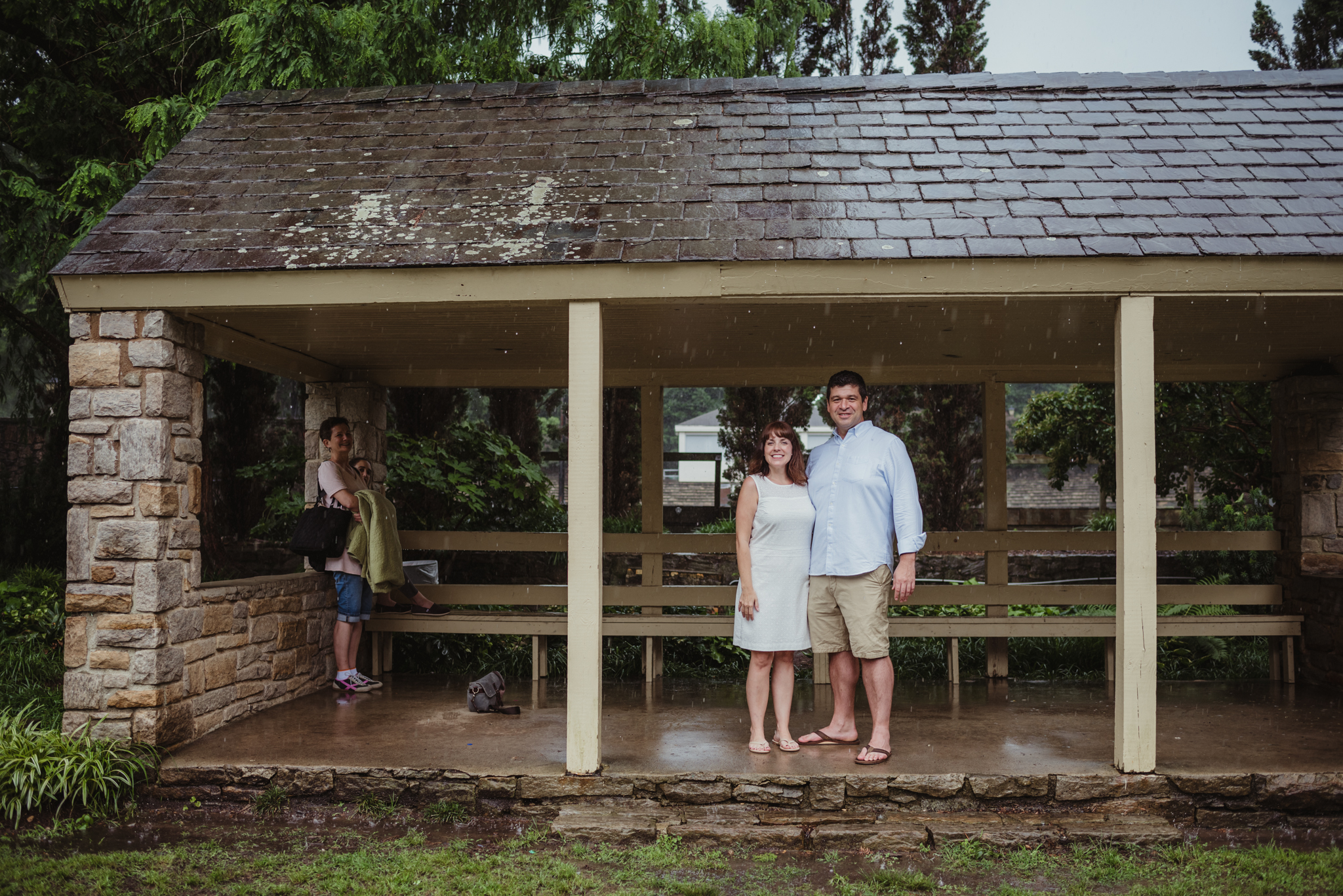 The bride and groom to be wait out the rain in the shelter during the rainstorm in Raleigh, during their engagement session with Rose Trail Images.