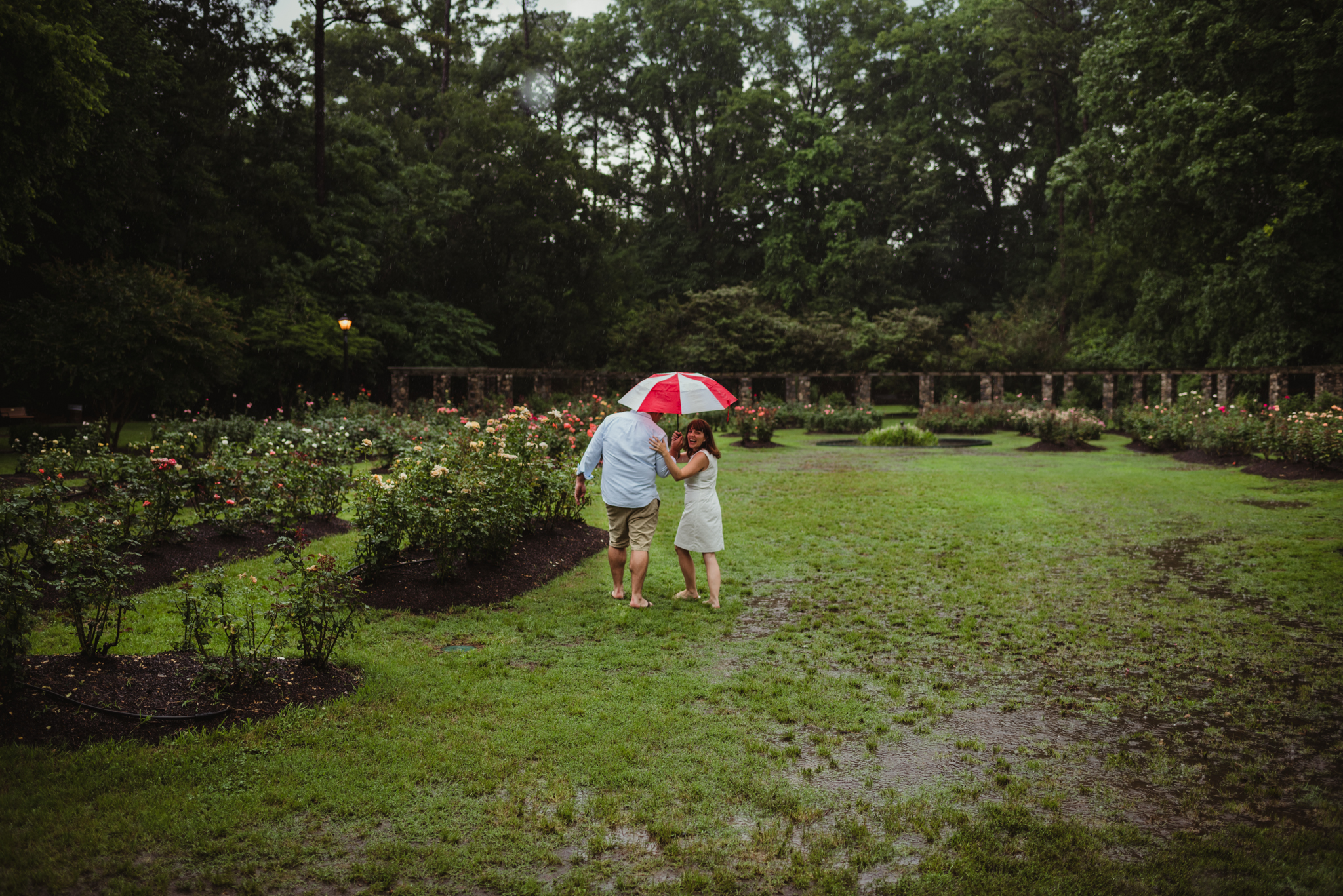 The bride and groom to be go under the umbrella during the rainstorm in Raleigh, during their engagement session with Rose Trail Images.