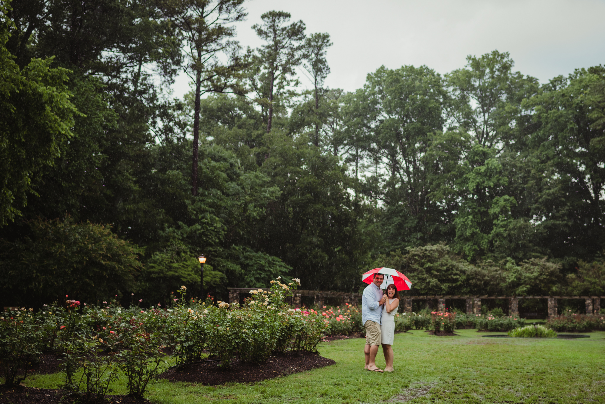 The bride and groom to be smile under the umbrella during the rainstorm in Raleigh, during their engagement session with Rose Trail Images.