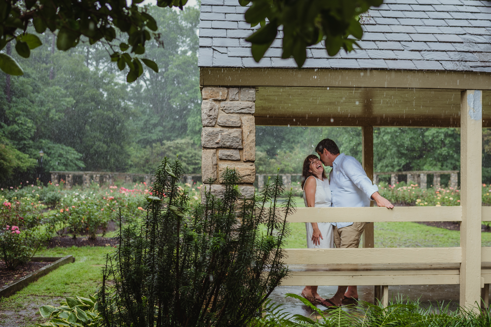 The bride and groom to be laugh together under the shelter during the rainstorm in Raleigh, during their engagement session with Rose Trail Images.