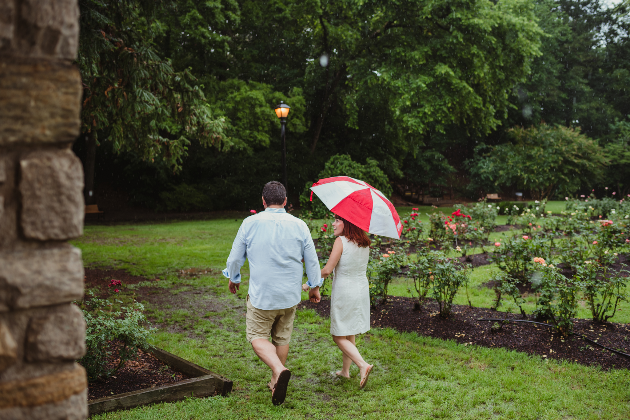 The bride and groom to be go walk under the umbrella during the rainstorm in Raleigh, during their engagement session with Rose Trail Images.