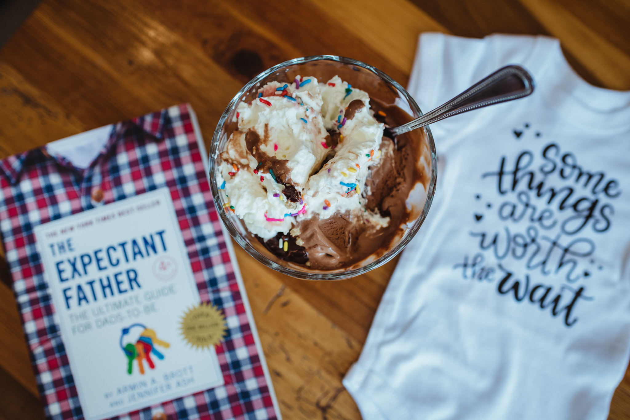 Details of an ice cream sundae, a onesie, and the expectant father book, image by Rose Trail Images.