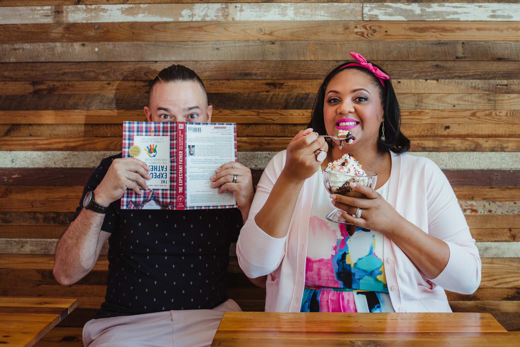 The parents to be sit at The Parlour in Durham and eat ice cream during their baby announcement photo session with Rose Trail Images.