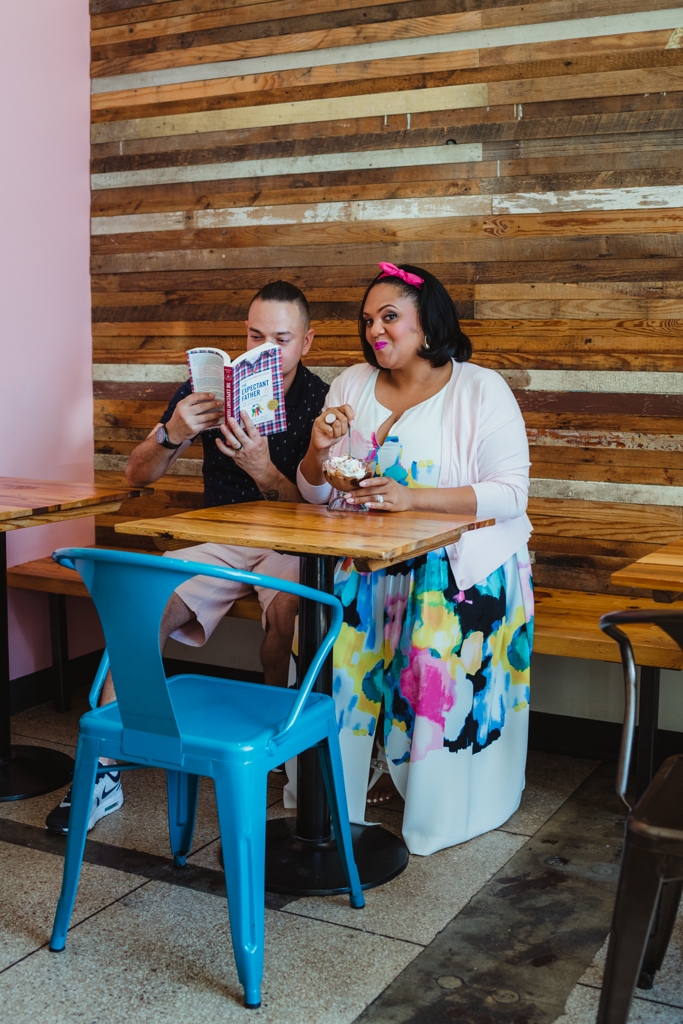 The mom to be sits eating ice cream at The Parlour in Durham while the dad to be reads a parenting book during their baby announcement photo session with Rose Trail Images.