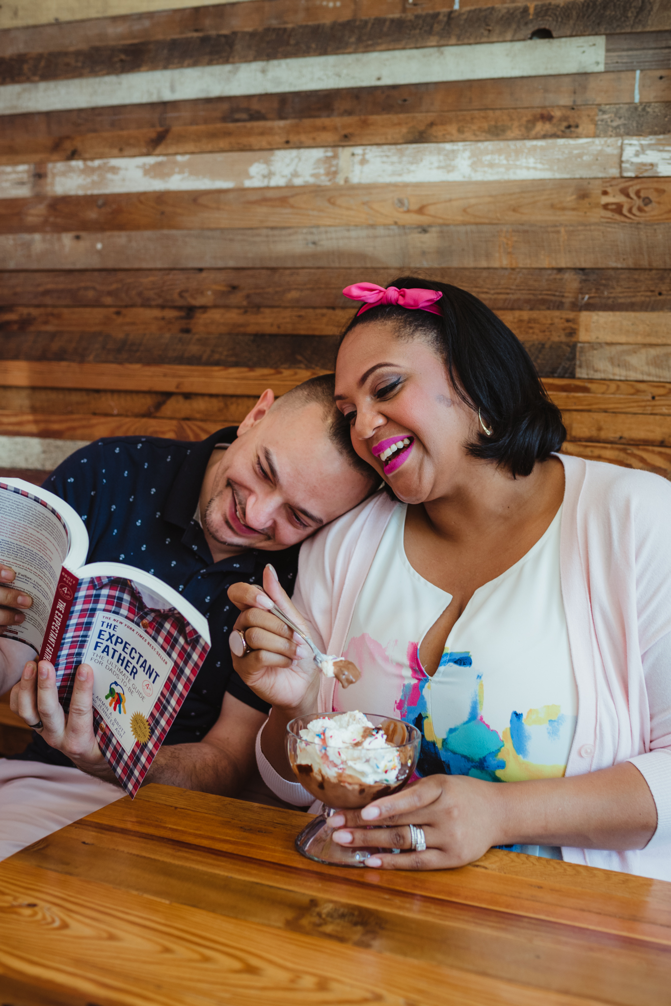 The parents to be read a parenting book and eat ice cream at The Parlour in Durham during their baby announcement photo session with Rose Trail Images.