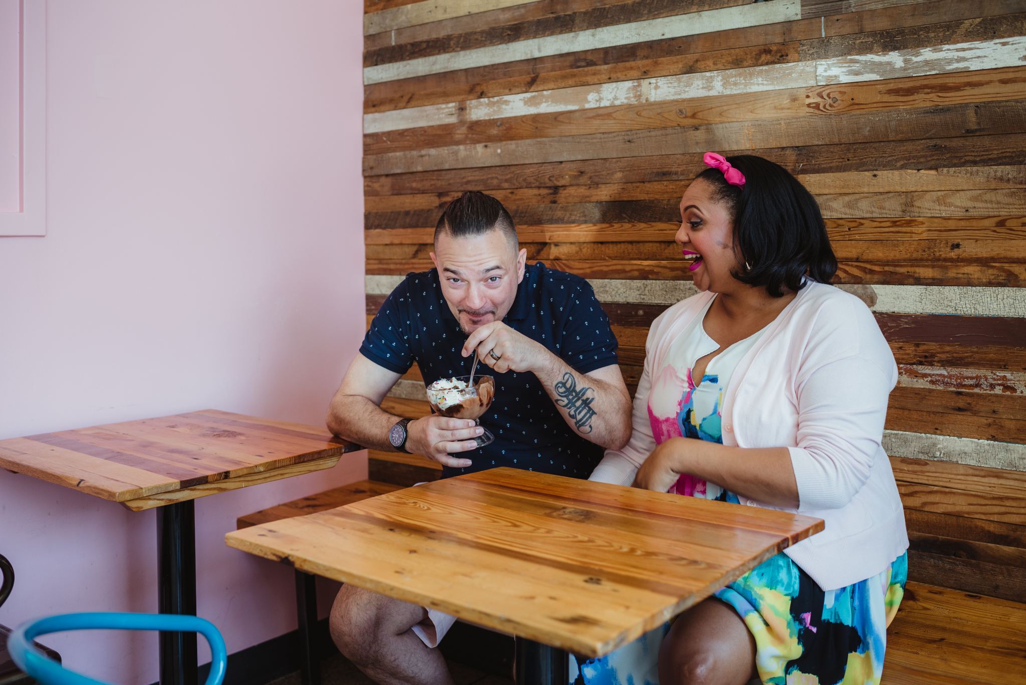 The dad to be steals the ice cream from the mom at The Parlour in Durham during their baby announcement photo session with Rose Trail Images.