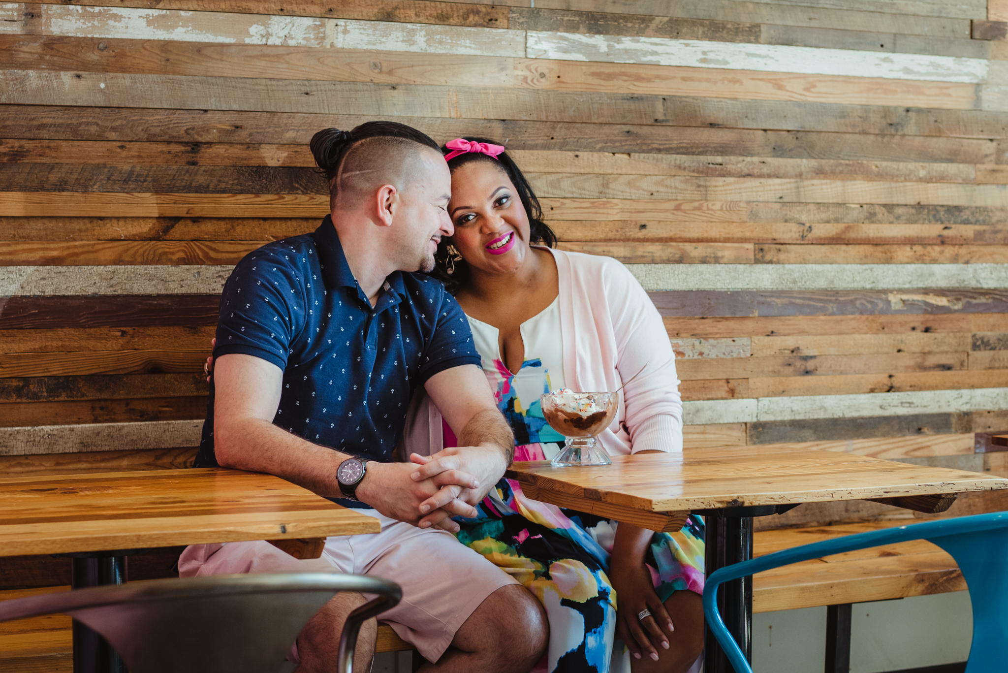 The parents to be cuddle together at The Parlour in Durham during their baby announcement photo session with Rose Trail Images.