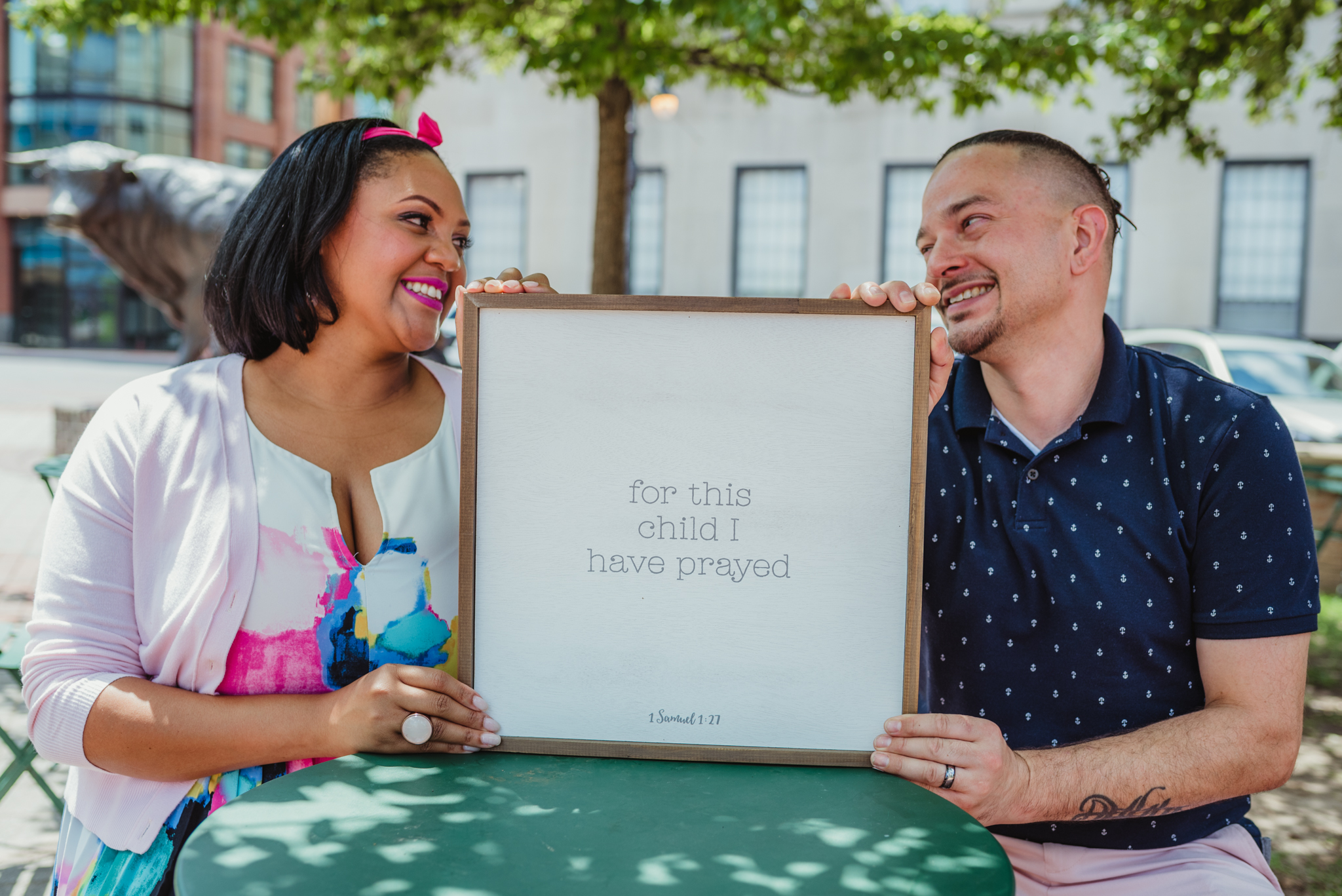 """The parents to be look at each other and hold a sign saying """"For this child I have prayed"""" outside in Durham during their baby announcement photo session with Rose Trail Images."""