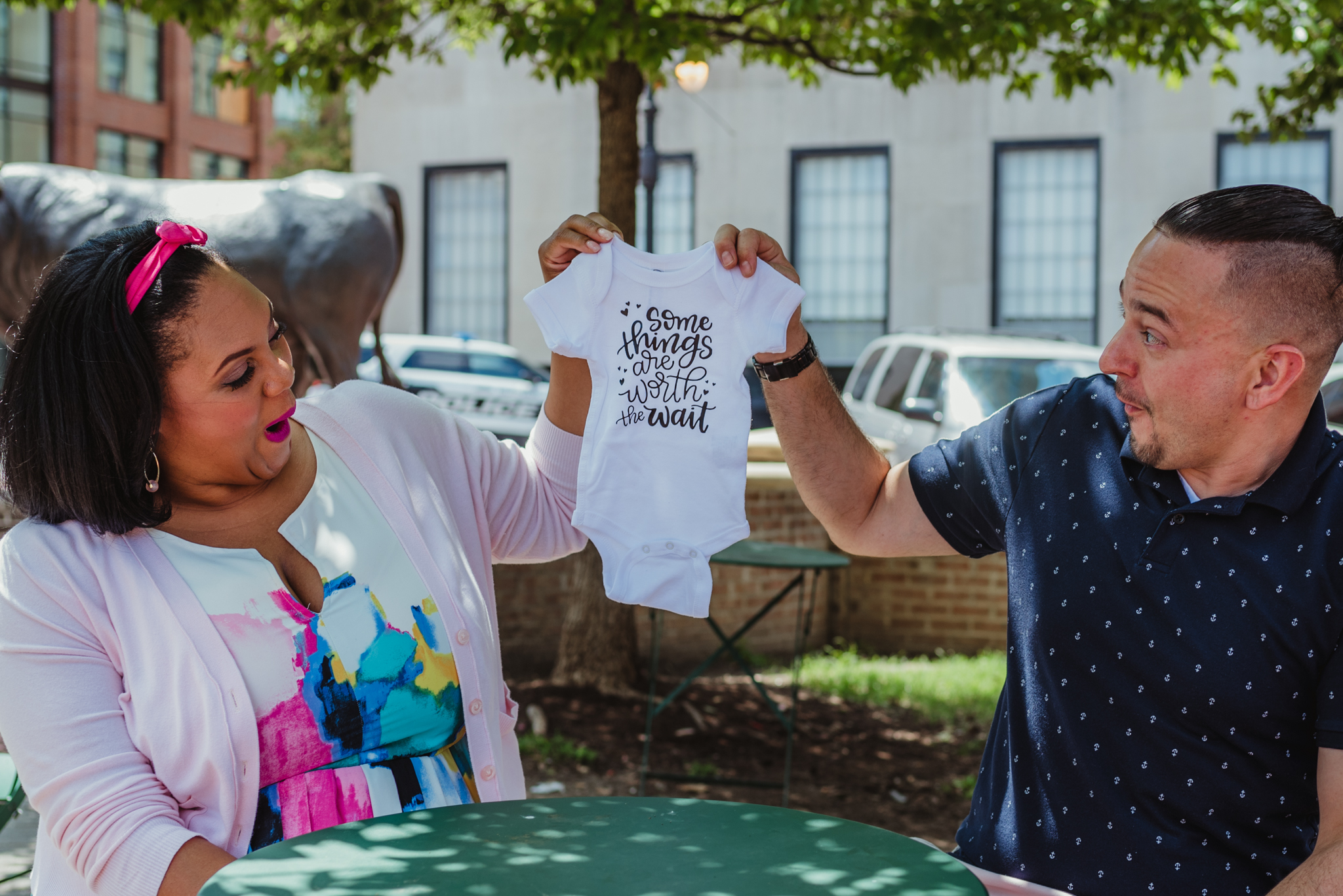 """The parents to be hold a onesie saying """"some things are worth the wait"""" outside in Durham during their baby announcement photo session with Rose Trail Images."""