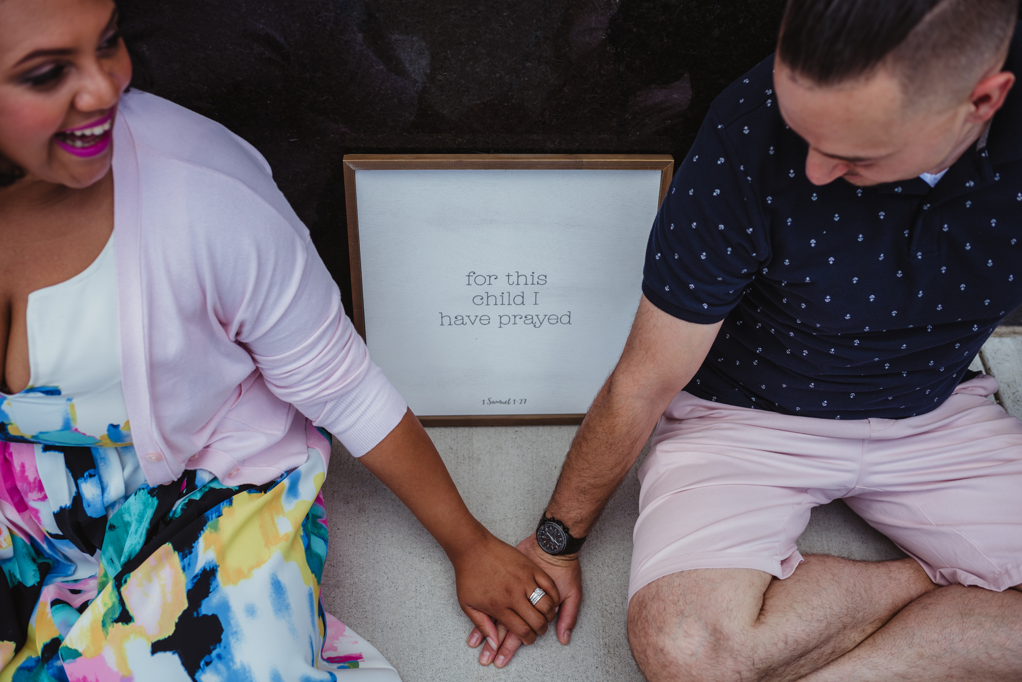 """The parents to be sit in front of a sign that says """"for this child I have prayed"""" outside in Durham during their baby announcement photo session with Rose Trail Images."""