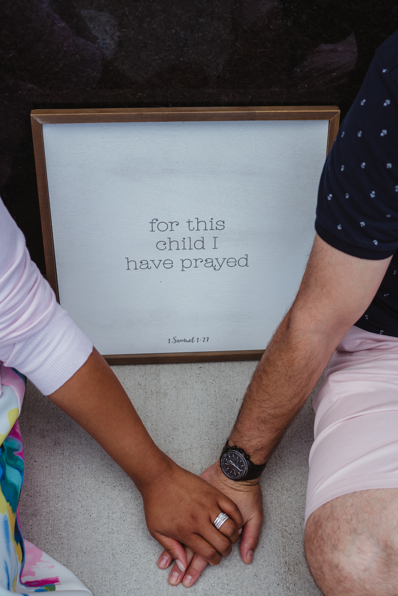 """The parents to be hold hands in front of a sign that says """"for this child I have prayed"""" outside in Durham during their baby announcement photo session with Rose Trail Images."""