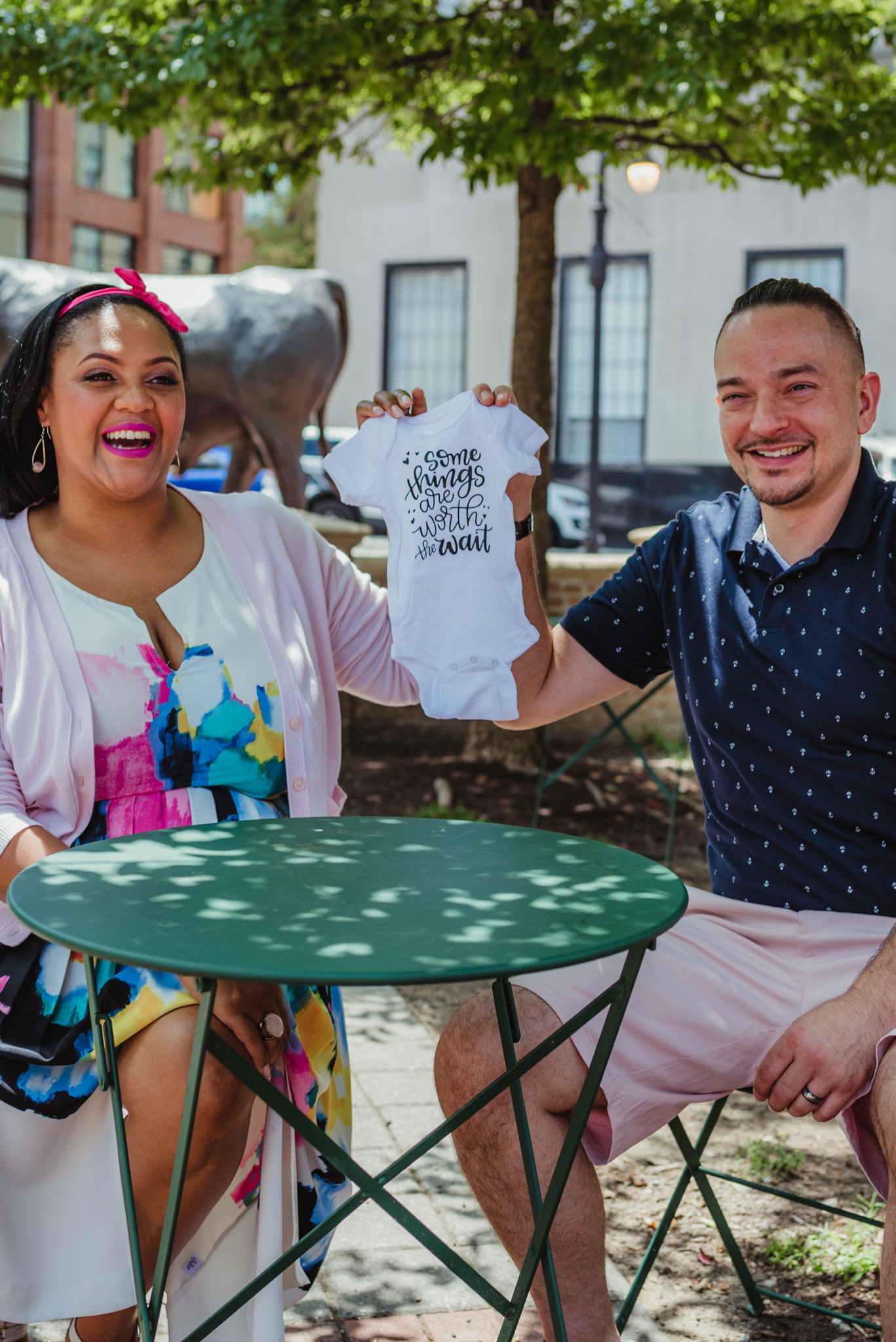 """The parents to be laugh together and hold a onesie saying """"some things are worth the wait"""" outside in Durham during their baby announcement photo session with Rose Trail Images."""