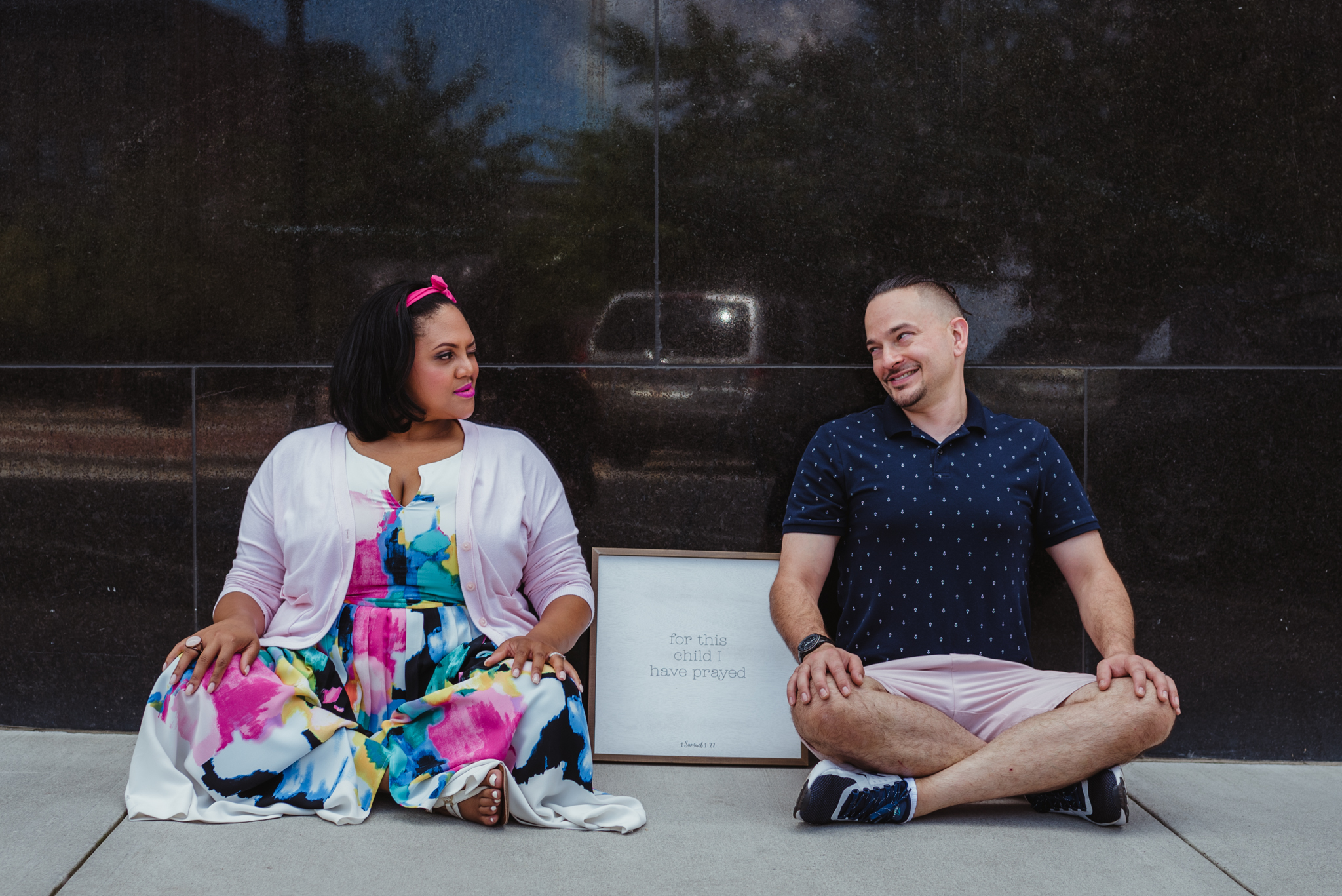 """The parents to be sit by a sign that says """"for this child I have prayed"""" outside in Durham during their baby announcement photo session with Rose Trail Images."""