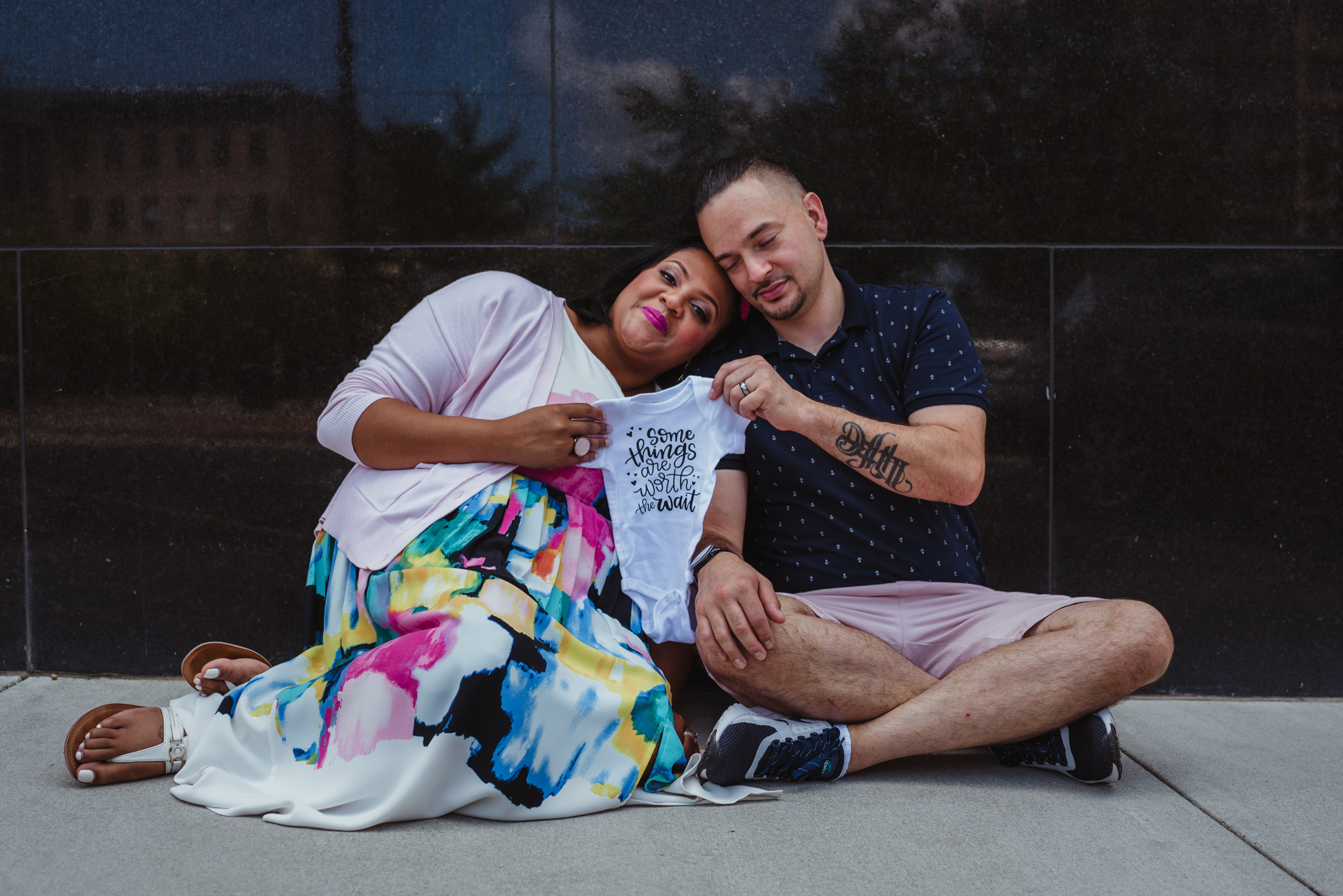 """The parents to be sit on the sidewalk holding a onesie that says """"some things are worth the wait"""" outside in Durham during their baby announcement photo session with Rose Trail Images."""
