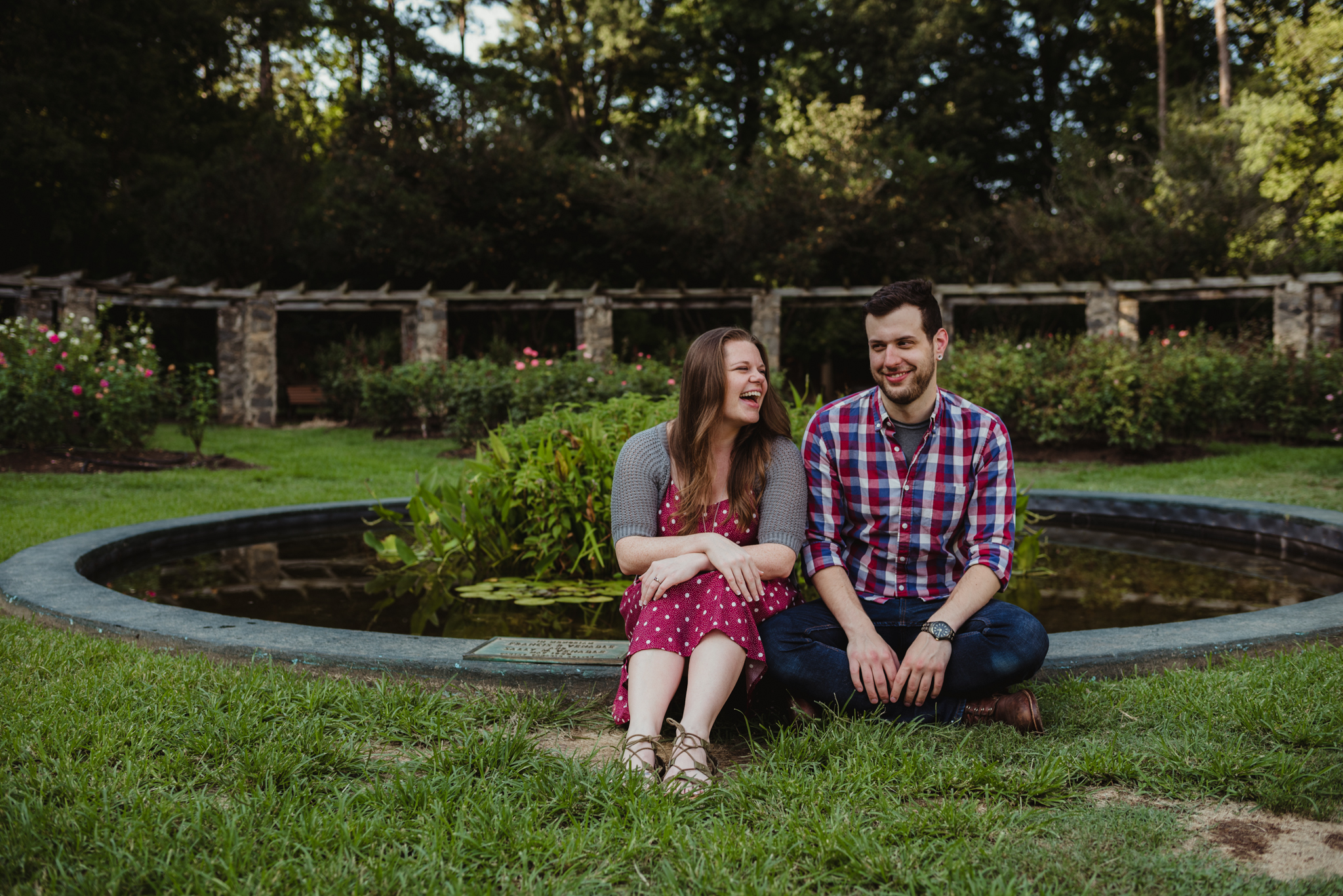 The bride and groom to be laugh with each other in front of the pond at the Raleigh Rose Garden during their engagement session with Rose Trail Images.