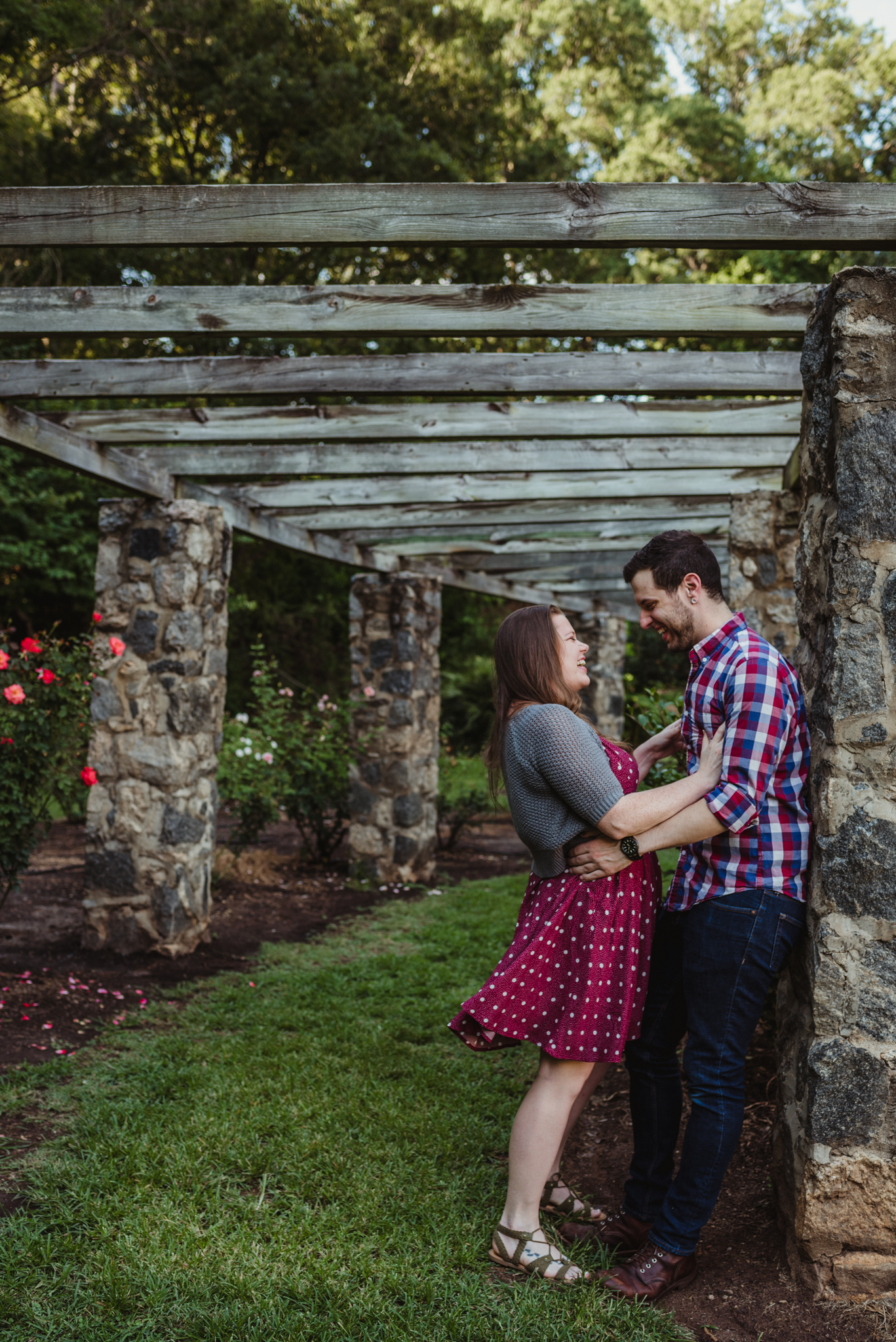 The bride and groom to be laugh with each other under the trellis while at the Raleigh Rose Garden during their engagement session with Rose Trail Images.