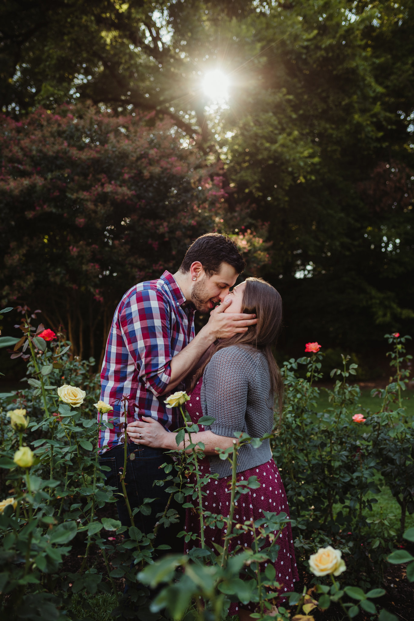The bride and groom to be almost kiss under the sunset at the Raleigh Rose Garden during their engagement session with Rose Trail Images.