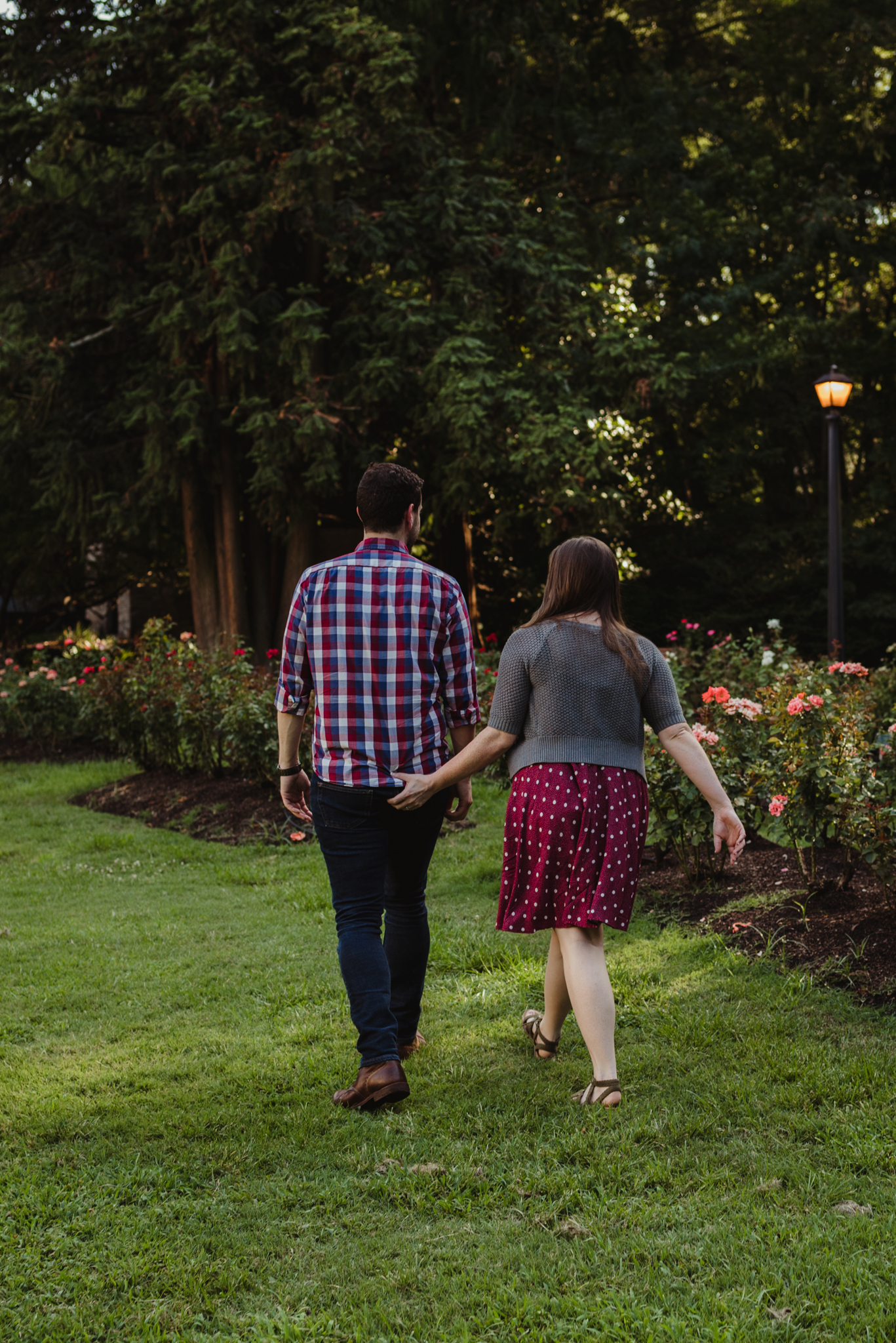 The bride to be grabs her fiance's but as they walk in the Raleigh Rose Garden during their engagement session with Rose Trail Images.