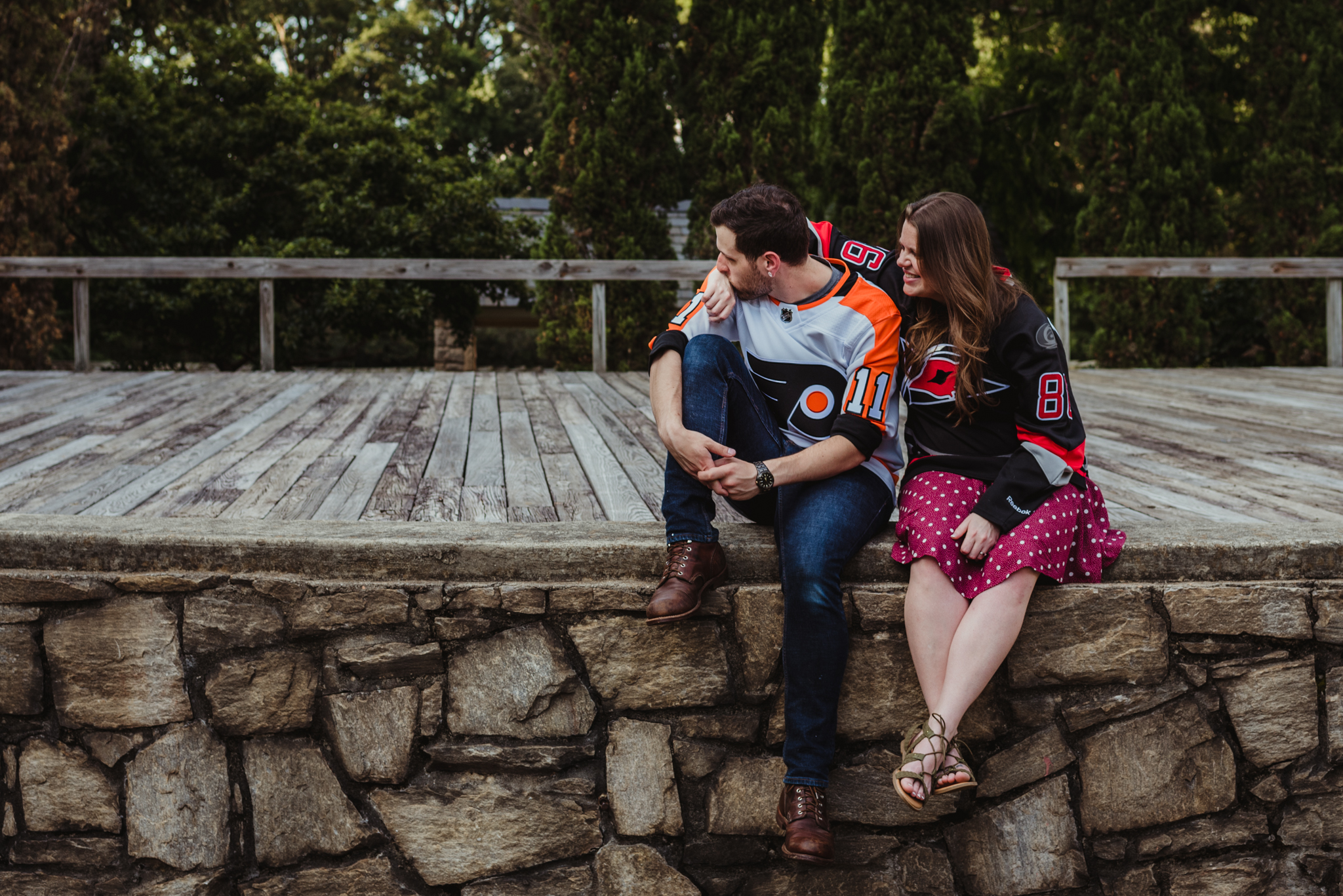 The bride and groom to be, in their Flyers and Hurricanes hockey jerseys, sit on the Little Theater stage at the Raleigh Rose Garden during their engagement session with Rose Trail Images.