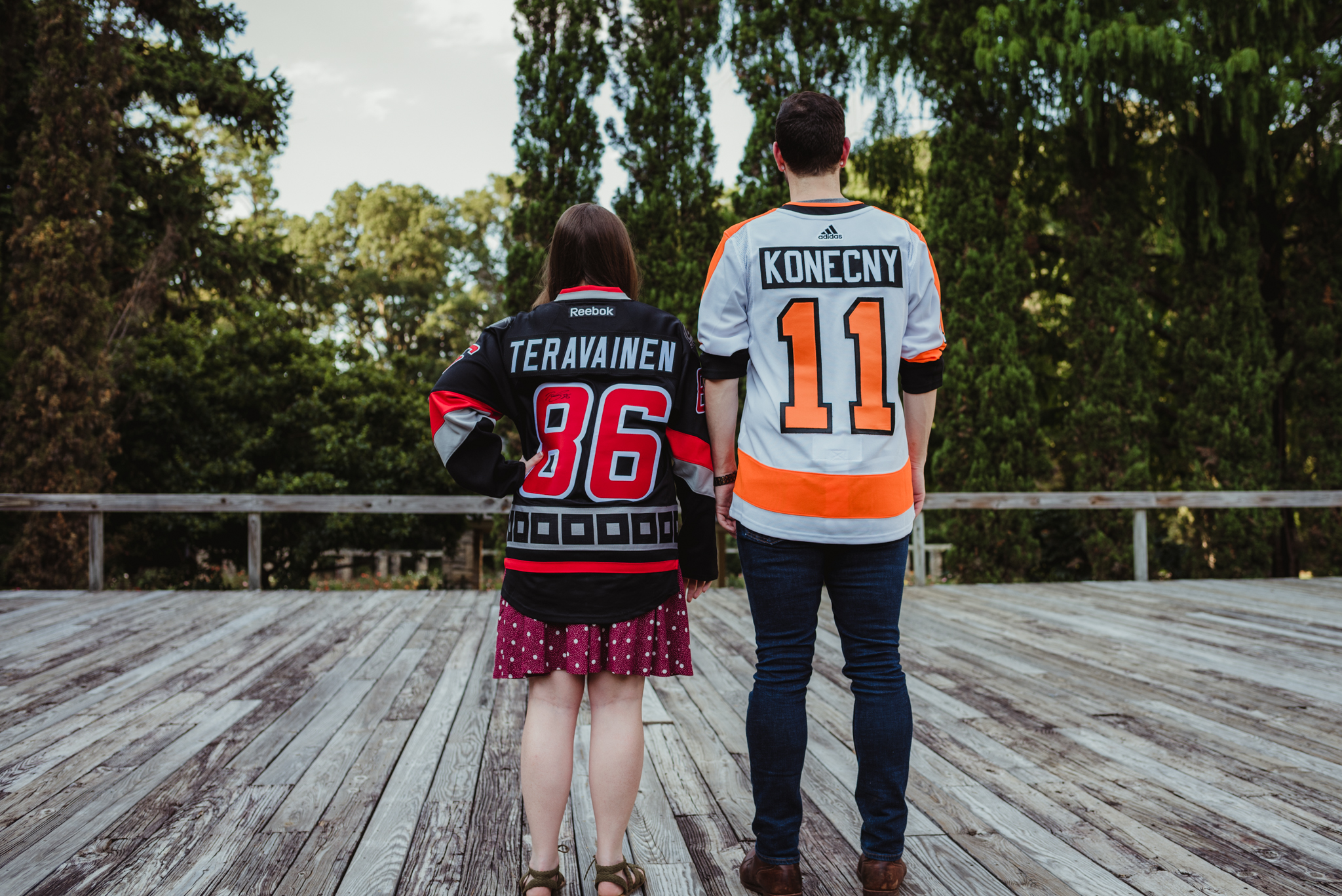 The bride and groom to be, in their Flyers and Hurricanes hockey jerseys, stand next to each other on the Little Theater stage at the Raleigh Rose Garden during their engagement session with Rose Trail Images.