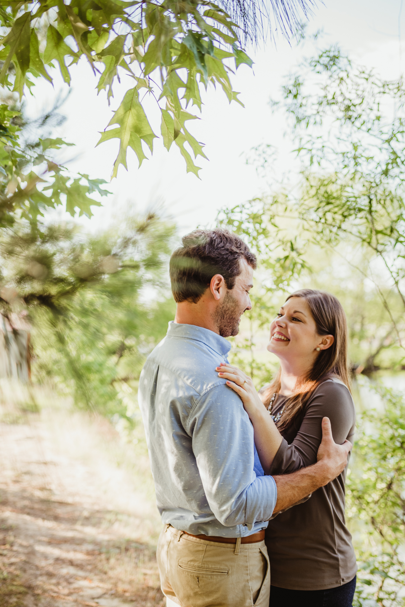 The bride and groom to be pose together on a dirt path for their engagement pictures with Rose Trail Images at their family farm in Benson, North Carolina.