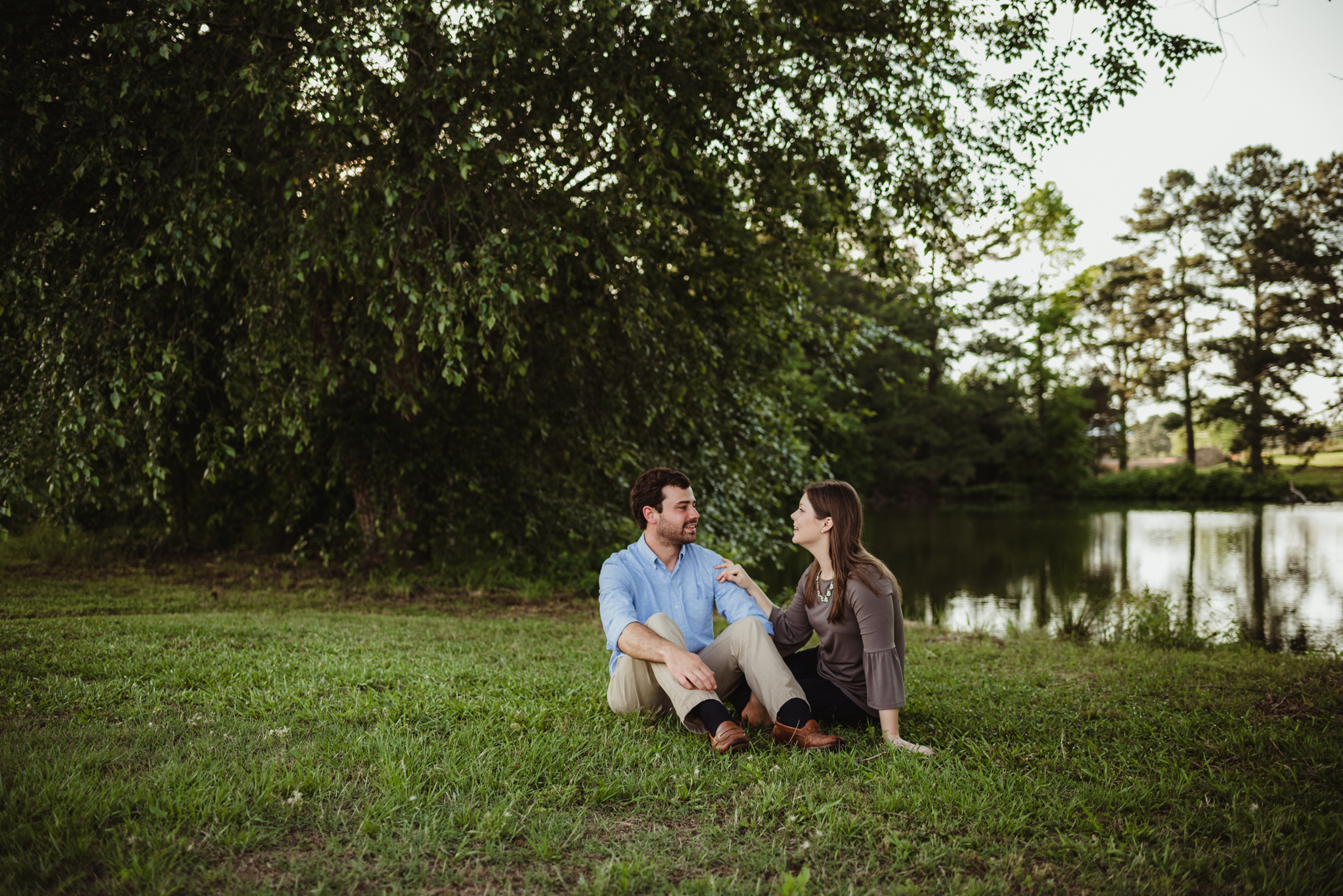 The bride and groom to be sit together for their engagement pictures with Rose Trail Images by the pond at their family farm in Benson, North Carolina.