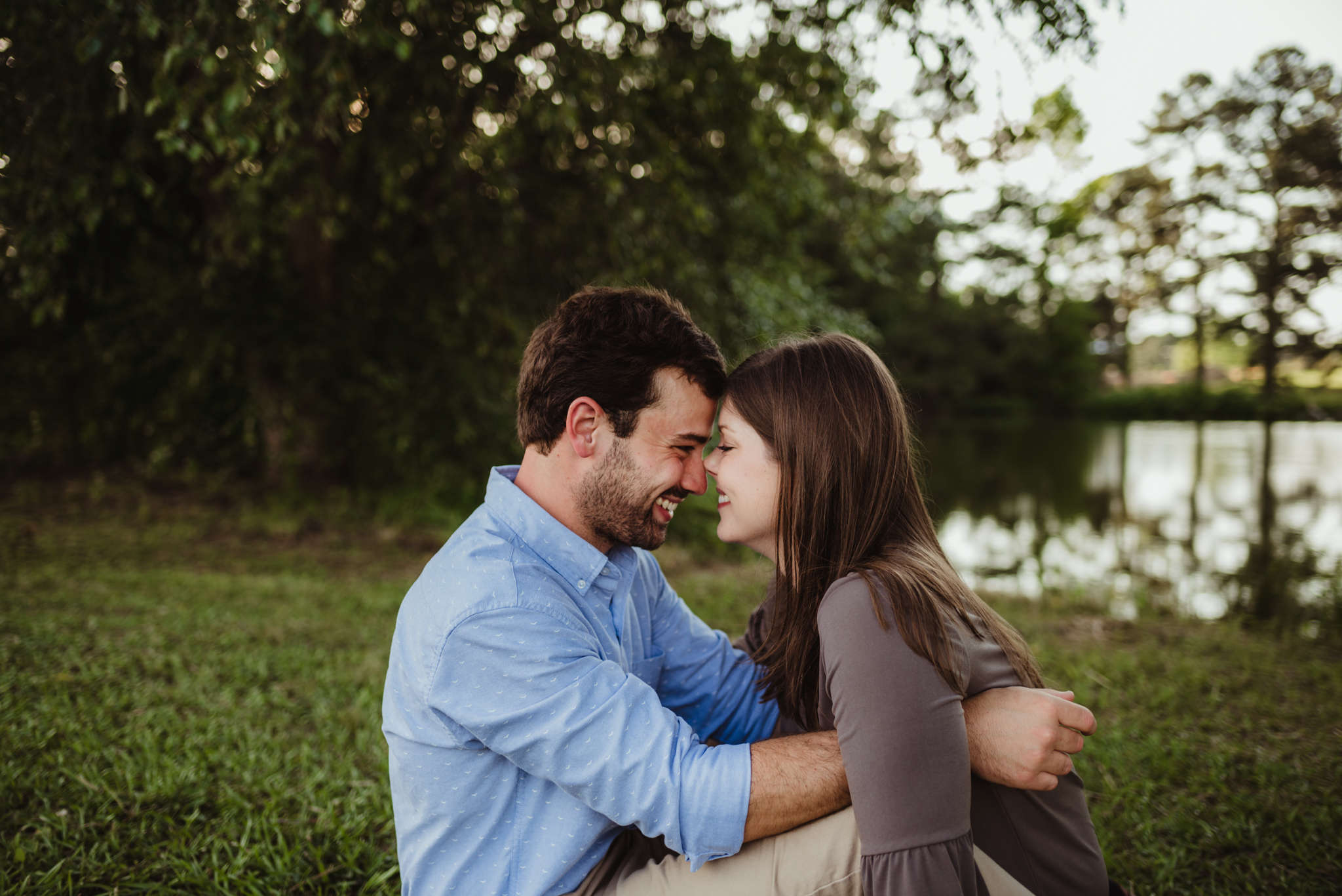 The bride and groom to be sit together and laugh during their engagement pictures with Rose Trail Images at their family farm in Benson, North Carolina.