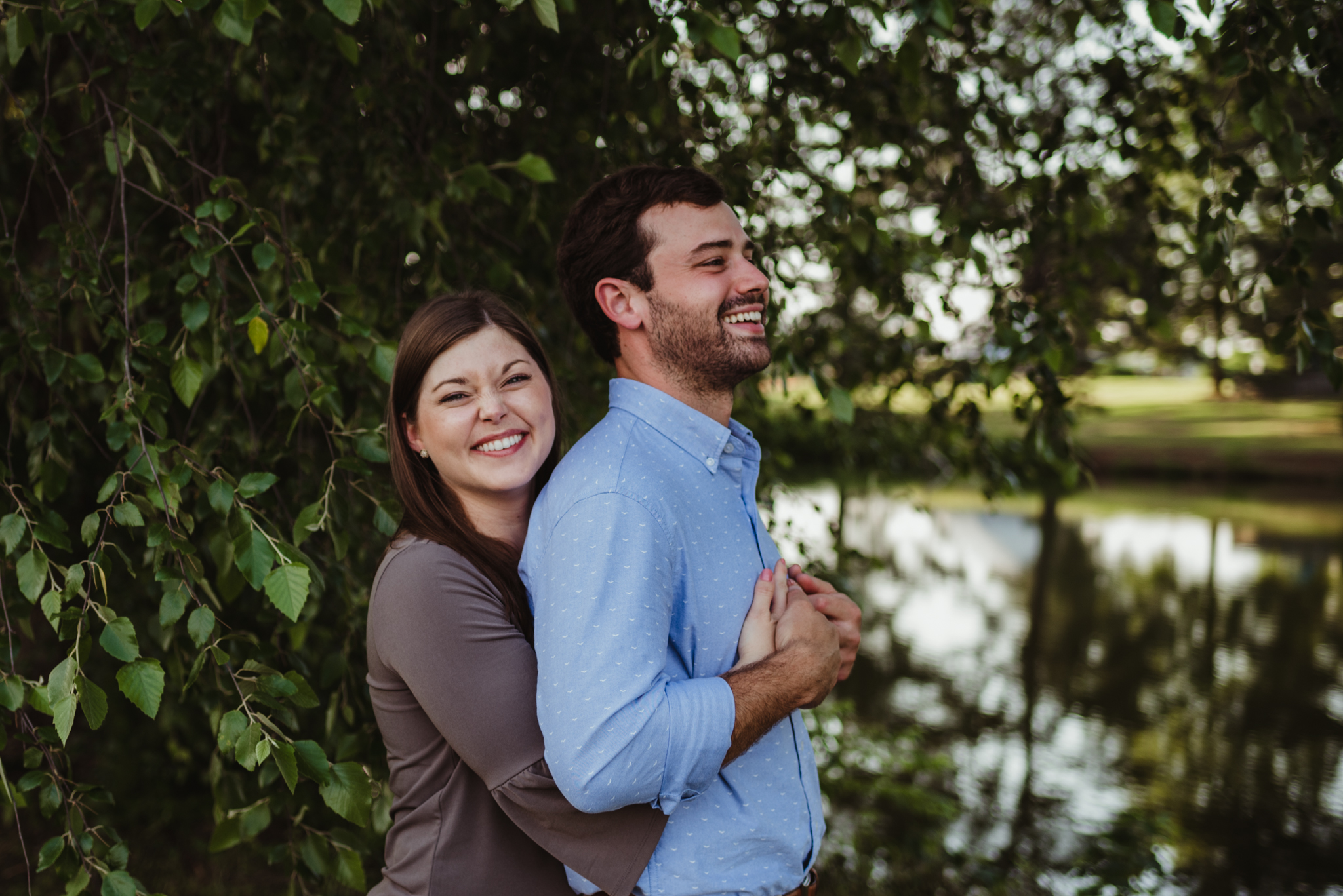 The bride and groom to be stand by the pond together for their engagement pictures with Rose Trail Images at their family farm in Benson, North Carolina.
