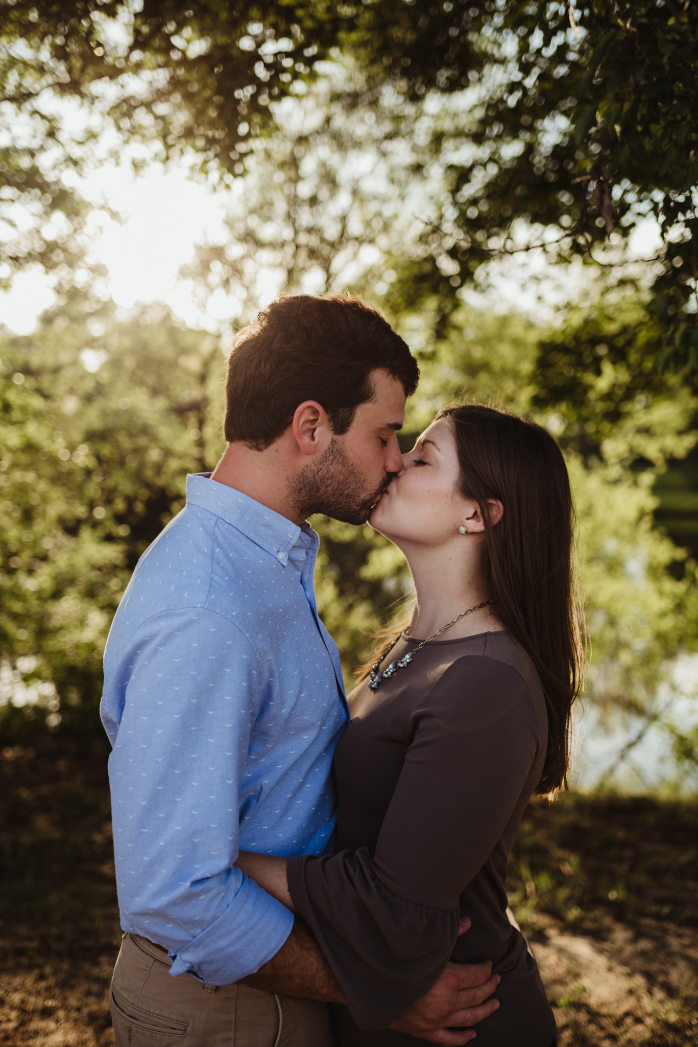 The bride and groom to be kiss under the sunset for their engagement pictures with Rose Trail Images at their family farm in Benson, North Carolina.
