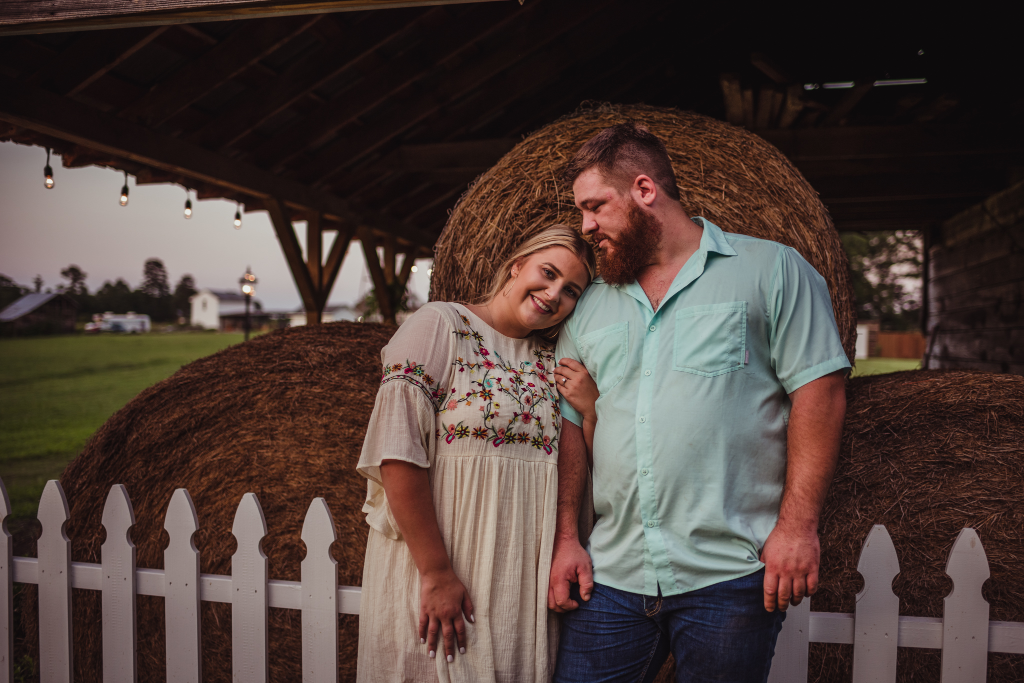 The future bride and groom snuggle up together by the hay bales at their wedding ceremony site for their engagement pictures with Rose Trail Images.