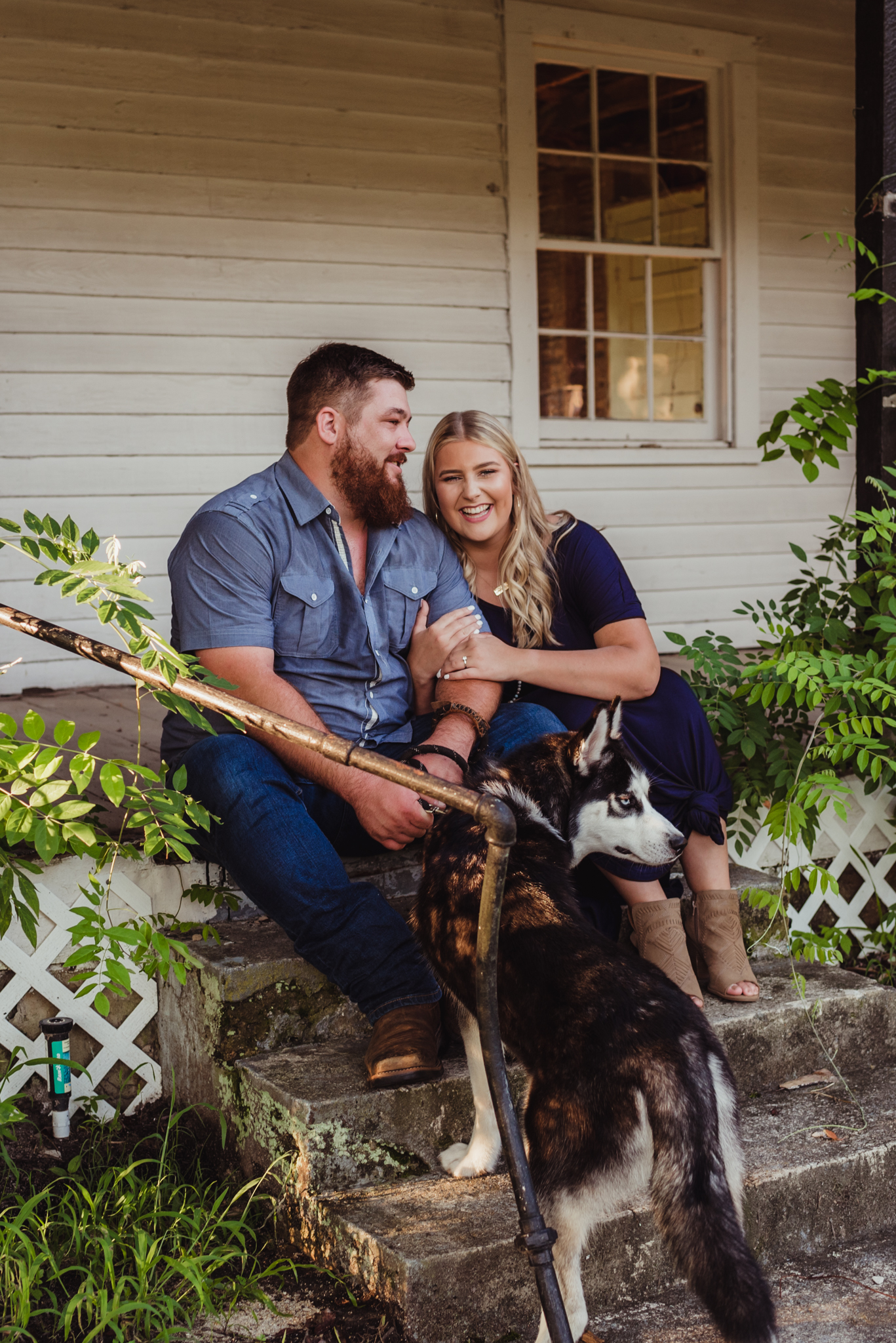 The future bride and groom snuggle up together with their husky pup for their engagement pictures with Rose Trail Images.