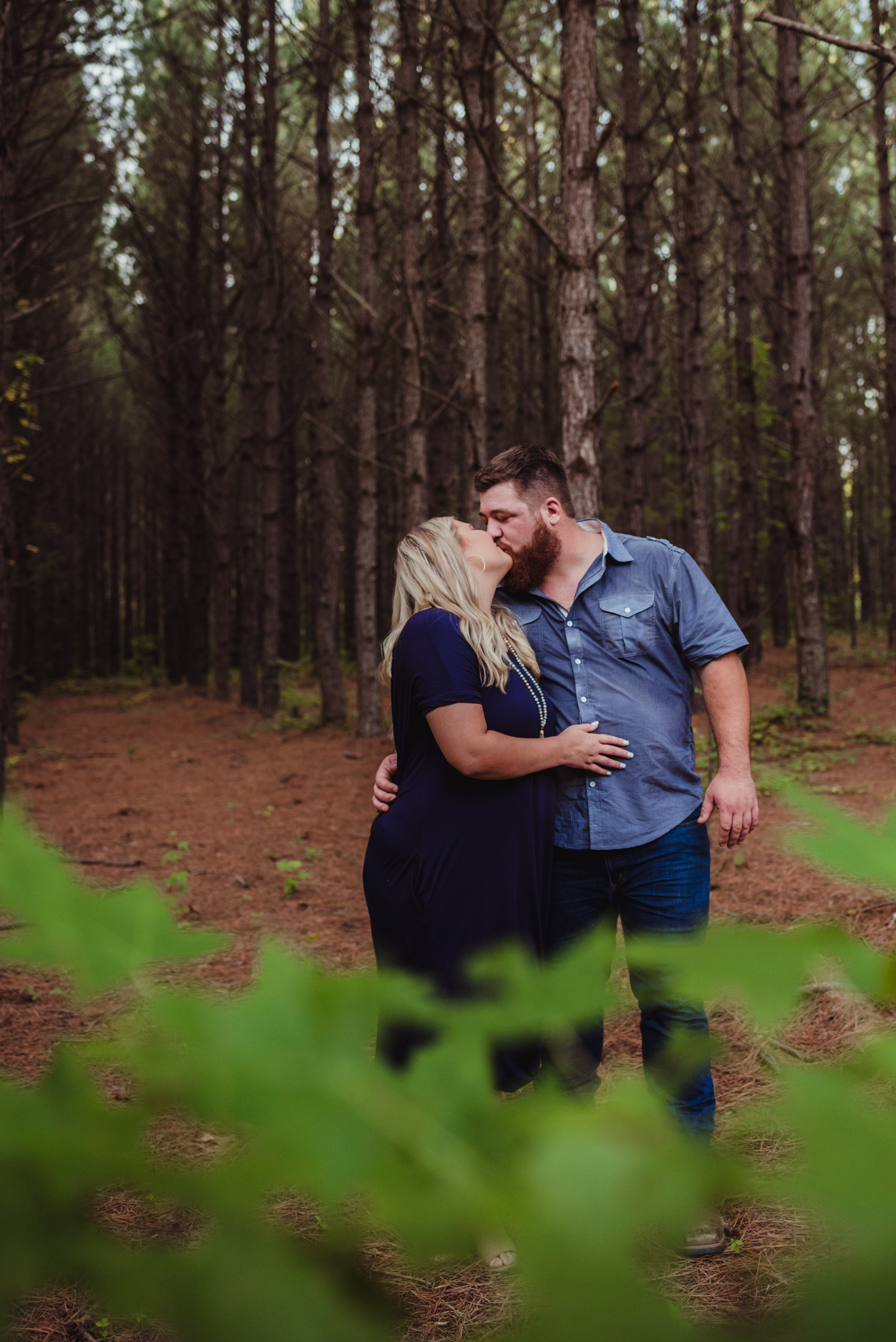 The future bride and groom share a kiss in the woods for their engagement pictures with Rose Trail Images.