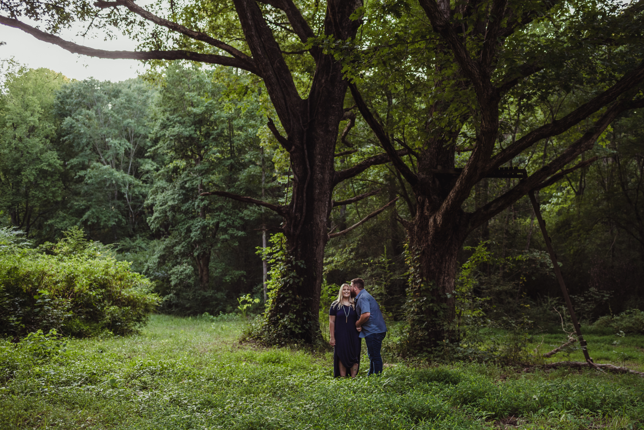 The future bride and groom kiss in the green woods at The Warren Estate for their engagement pictures with Rose Trail Images.