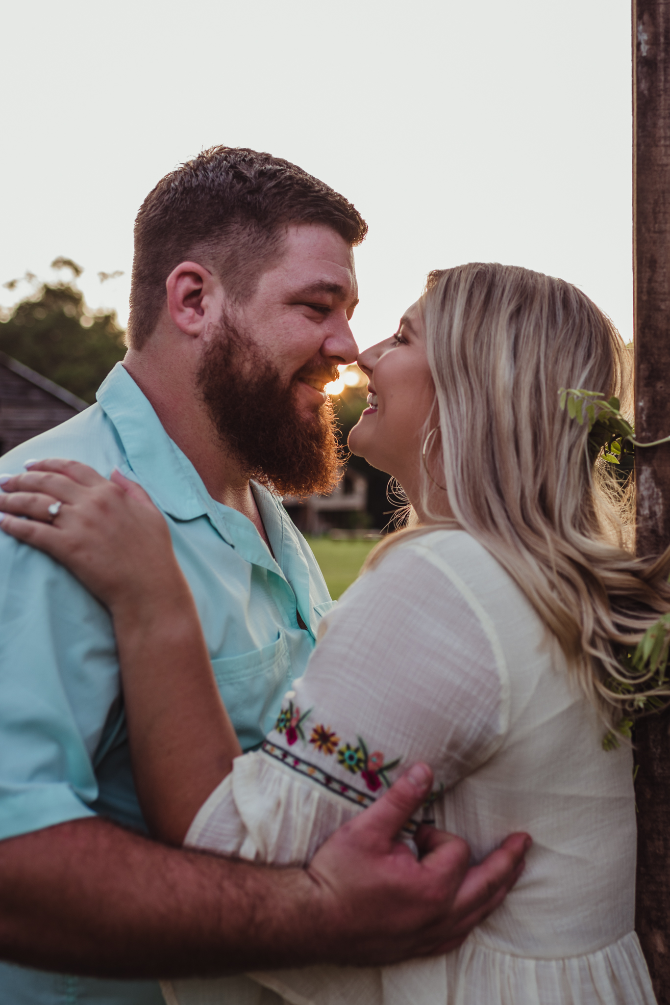 The future bride and groom smile at each other at sunset at the Warren Estate for their engagement pictures with Rose Trail Images.
