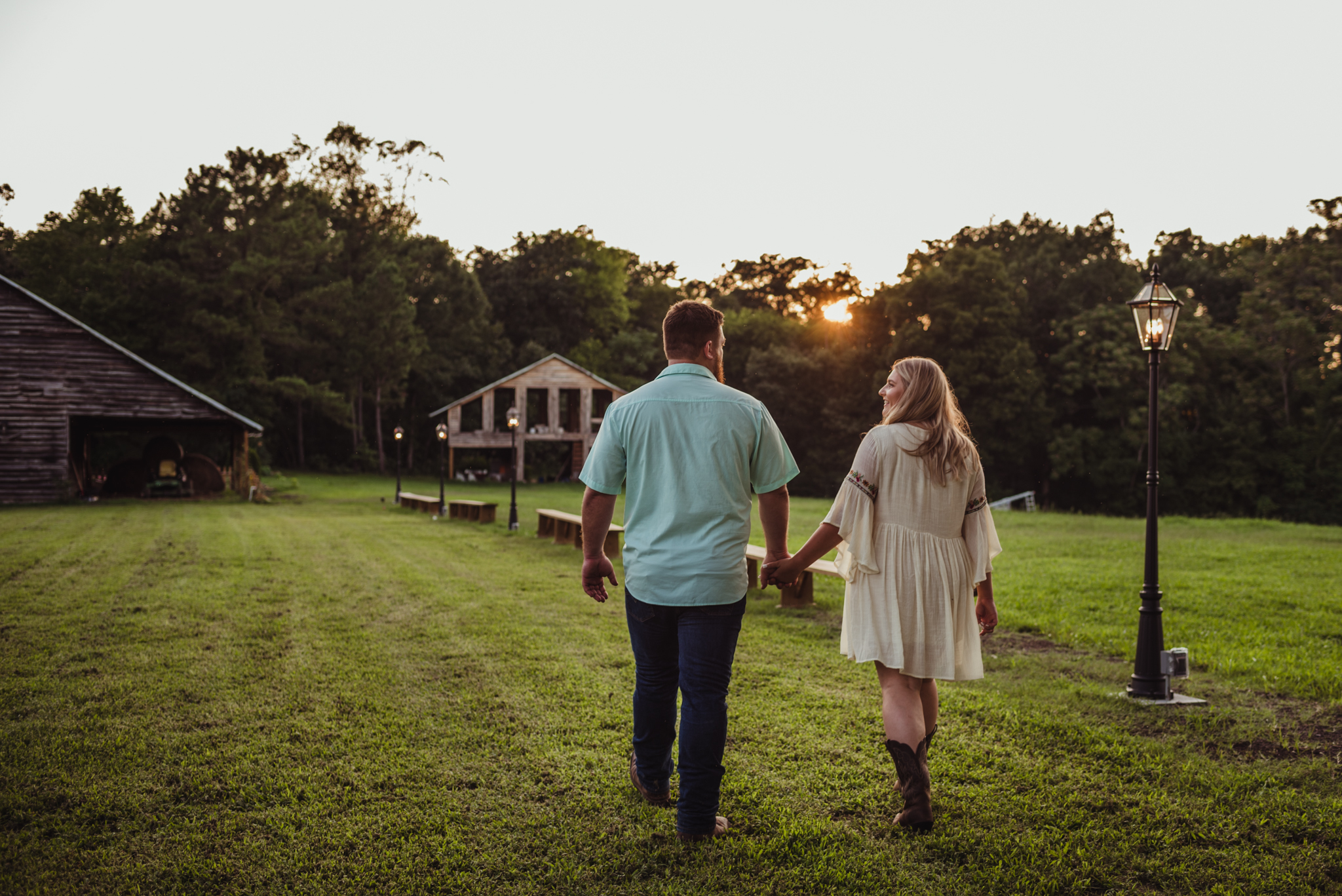 The future bride and groom walk to the barn at the Warren Estate during sunset for their engagement pictures with Rose Trail Images.