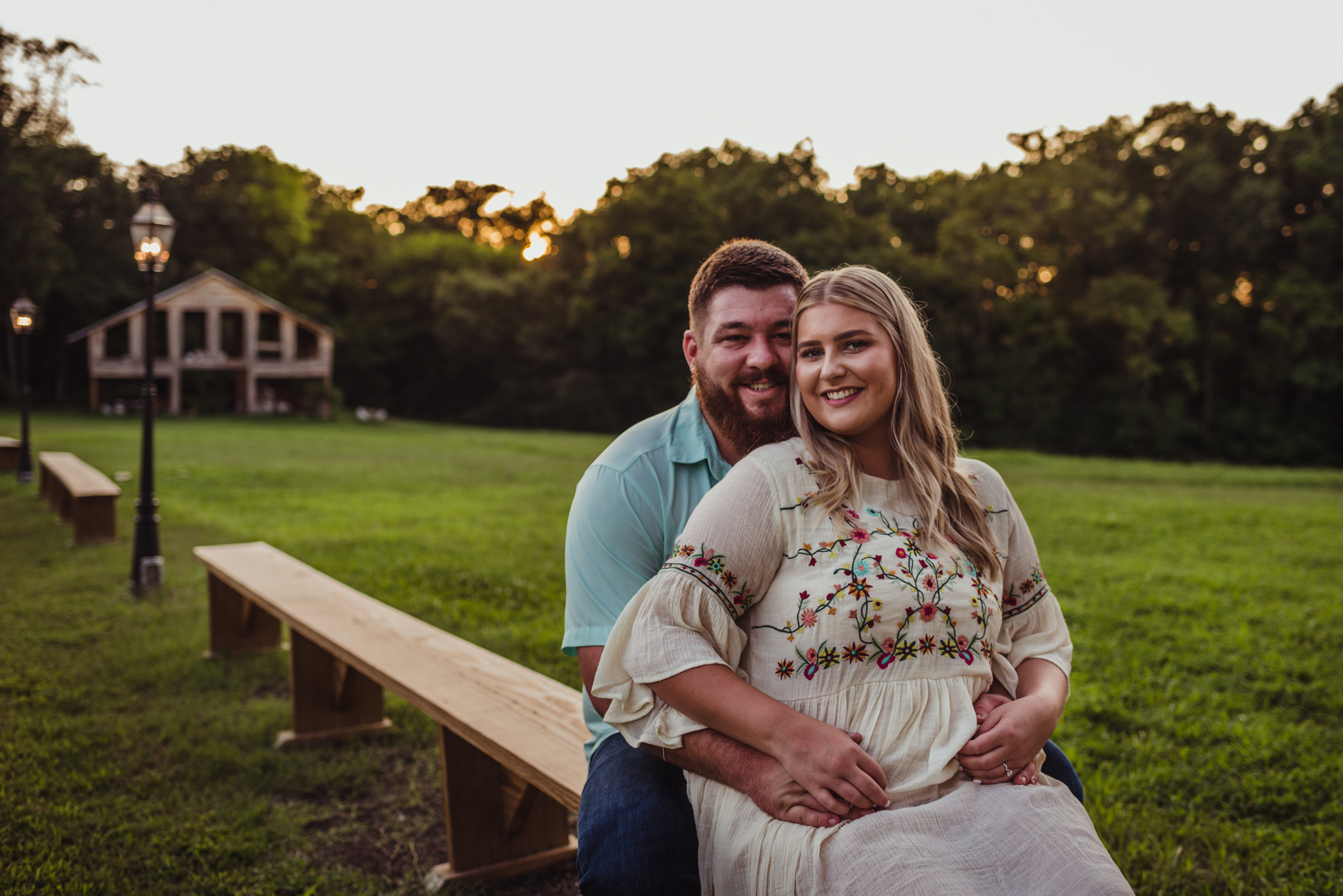 The future bride and groom sit by the barn at the Warren Estate during sunset for their engagement pictures with Rose Trail Images.