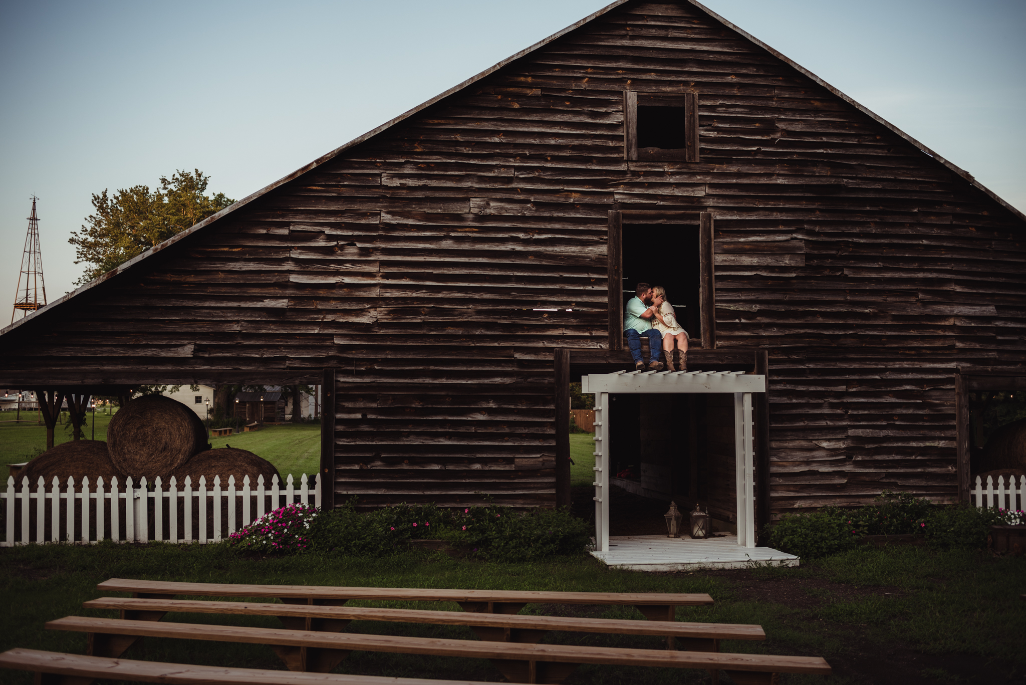 The future bride and groom sit above their wedding ceremony site at the Warren Estate during sunset for their engagement pictures with Rose Trail Images.
