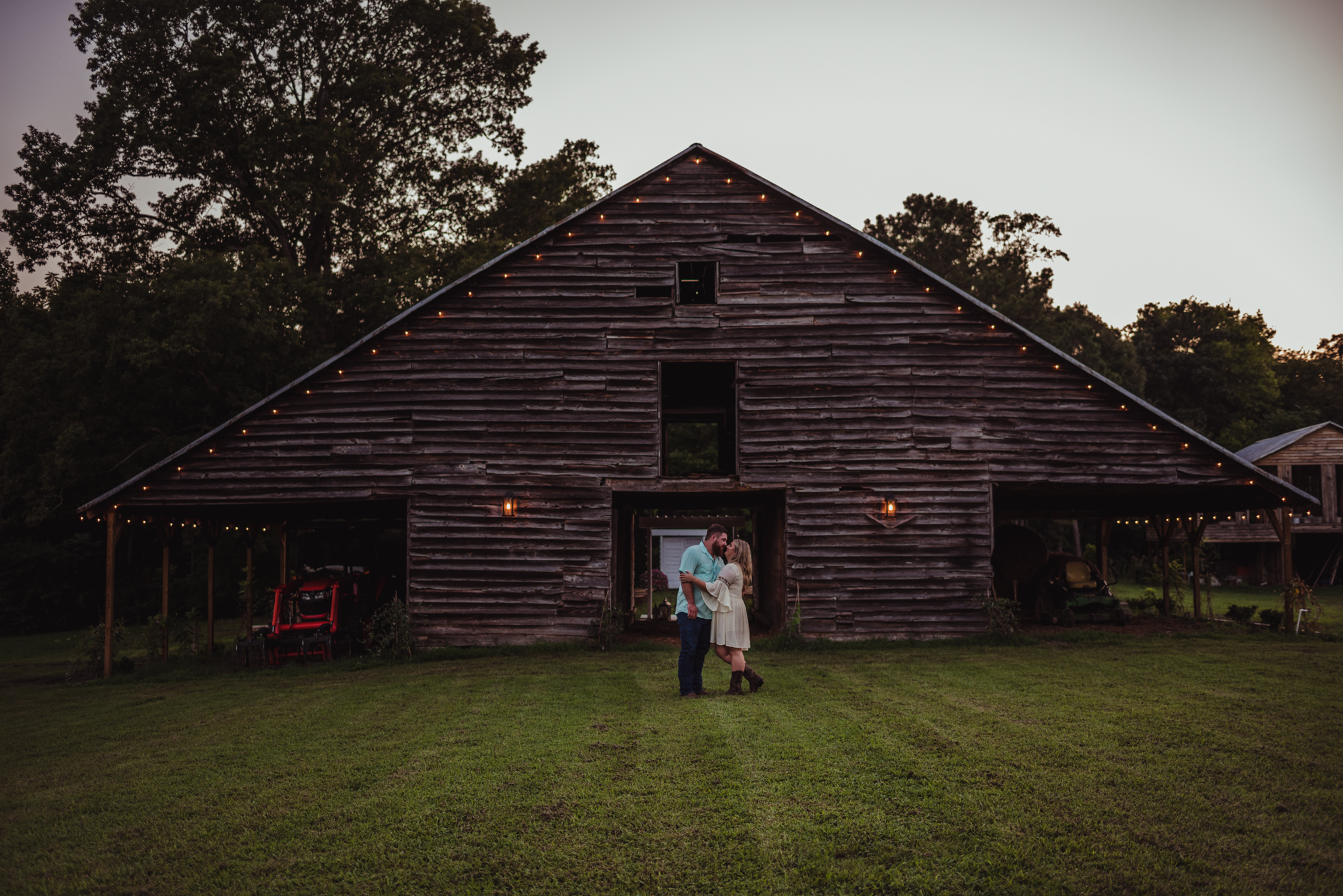 The future bride and groom kiss at sunset in front of the barn for their engagement pictures at The Warren Estate with Rose Trail Images.