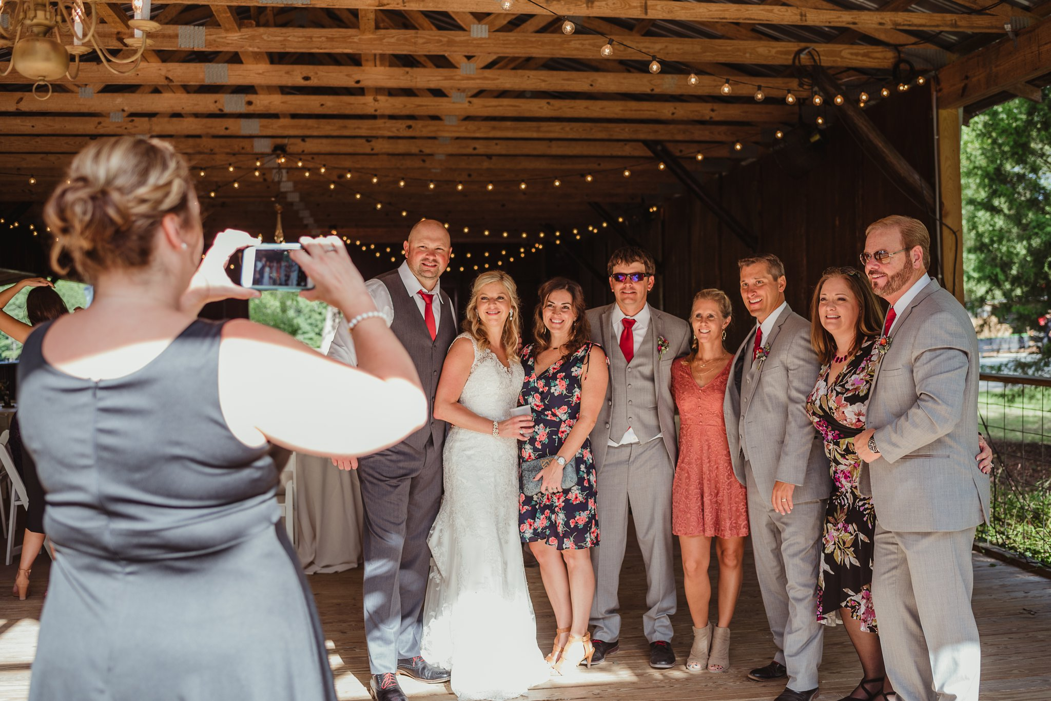 The bride and groom share a picture with friends during their wedding reception at Cedar Grove Acres near Raleigh, pictures by Rose Trail Images.