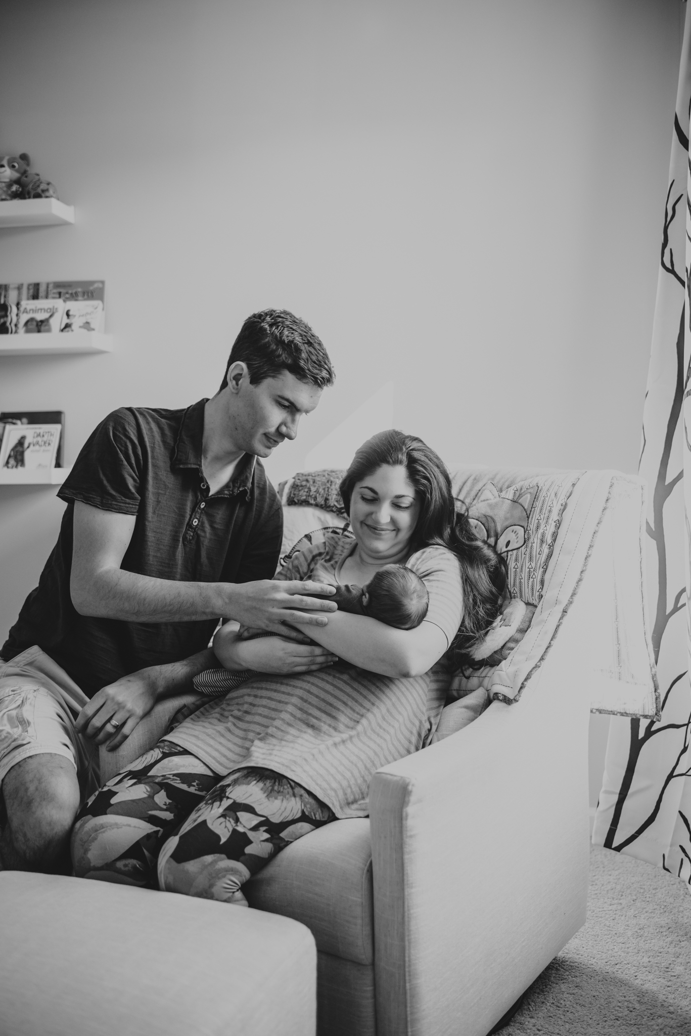 The new parents sit in the chair in the nursery while holding their newborn in Wake Forest, a black and white image by Rose Trail Images.
